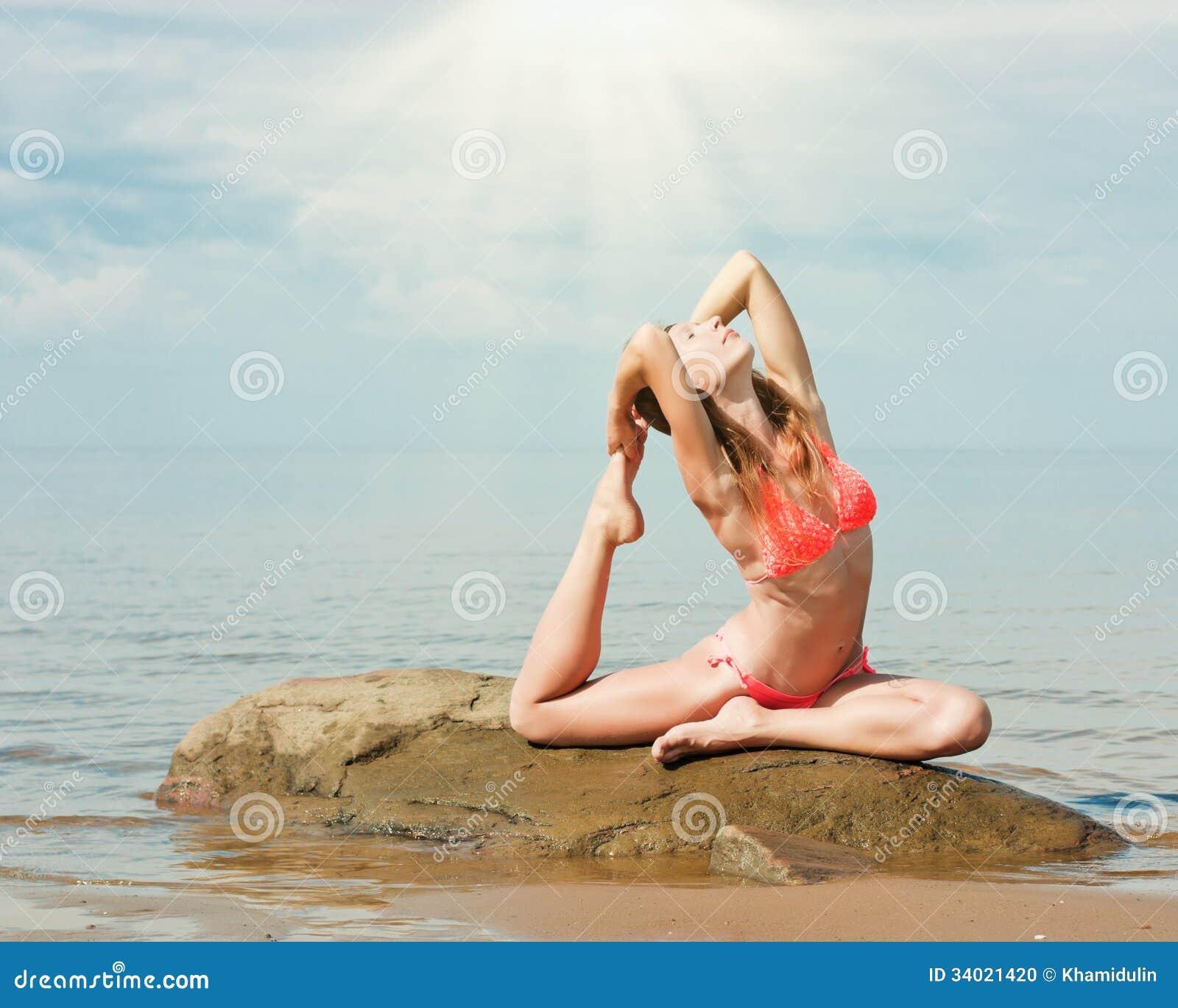 Красивая йога женщины на пляже