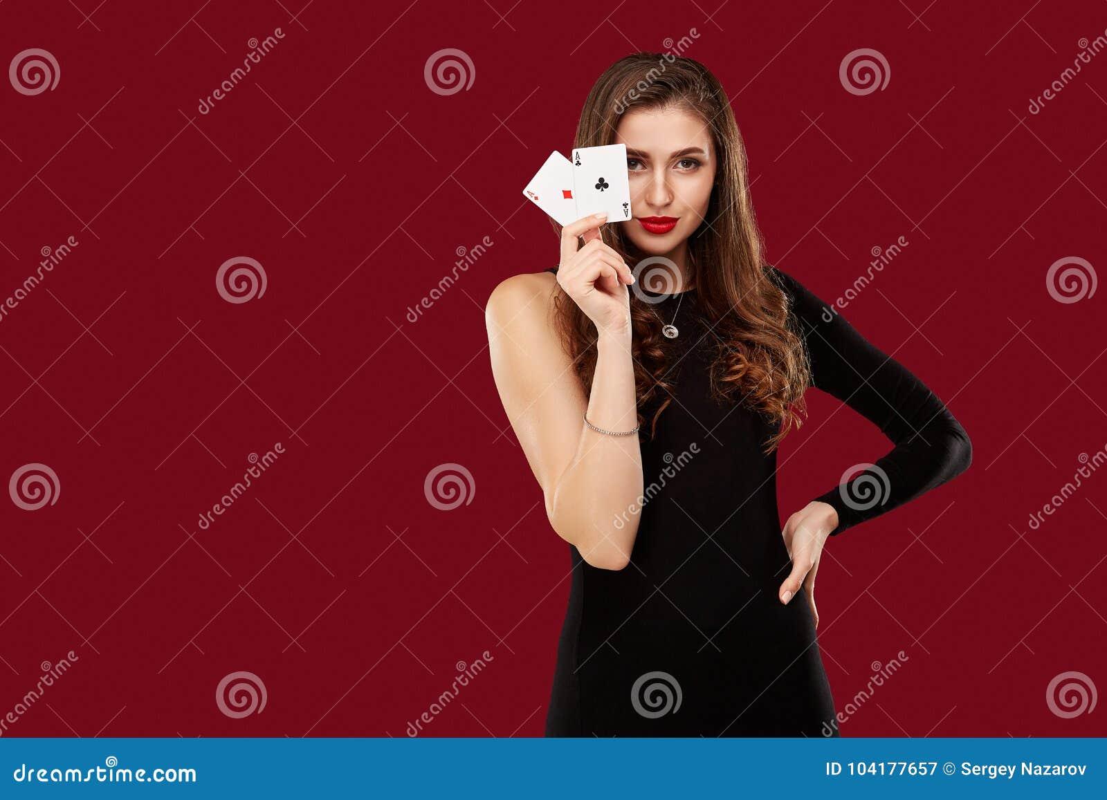 Красивая кавказская женщина в черном платье с покером чешет играть в азартные игры в казино