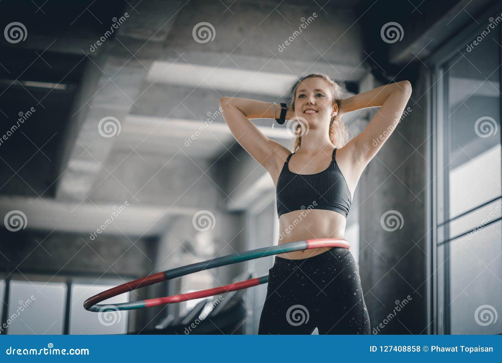 Красивая кавказская молодая женщина делая обруч hula в талии шага hooping передняя позиция Молодая женщина делая обруч hula