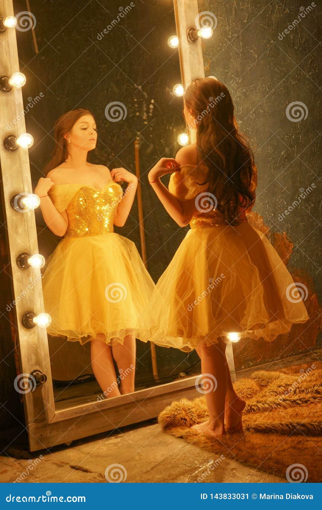 Красивая маленькая девочка в платье вечера золота стоит на половике меха около большого зеркала в рамке со светами и взглядами в