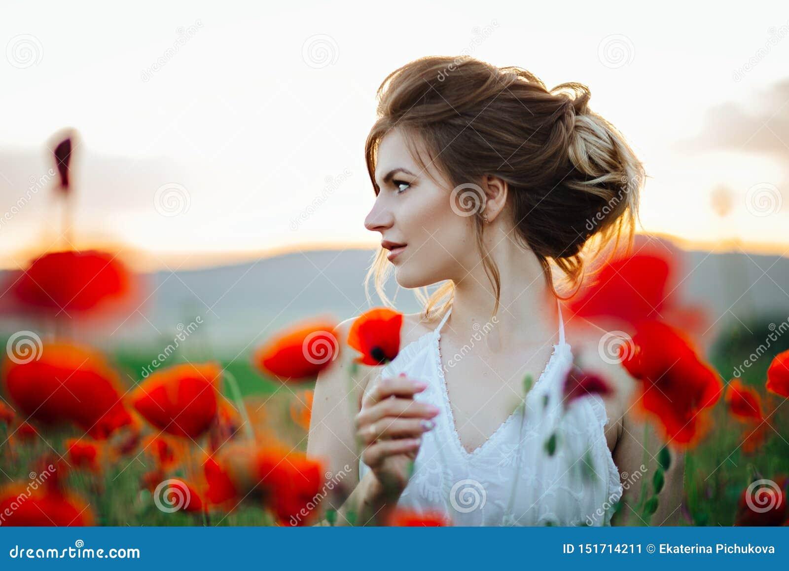 Красивая маленькая девочка в полях мака на заходе солнца E