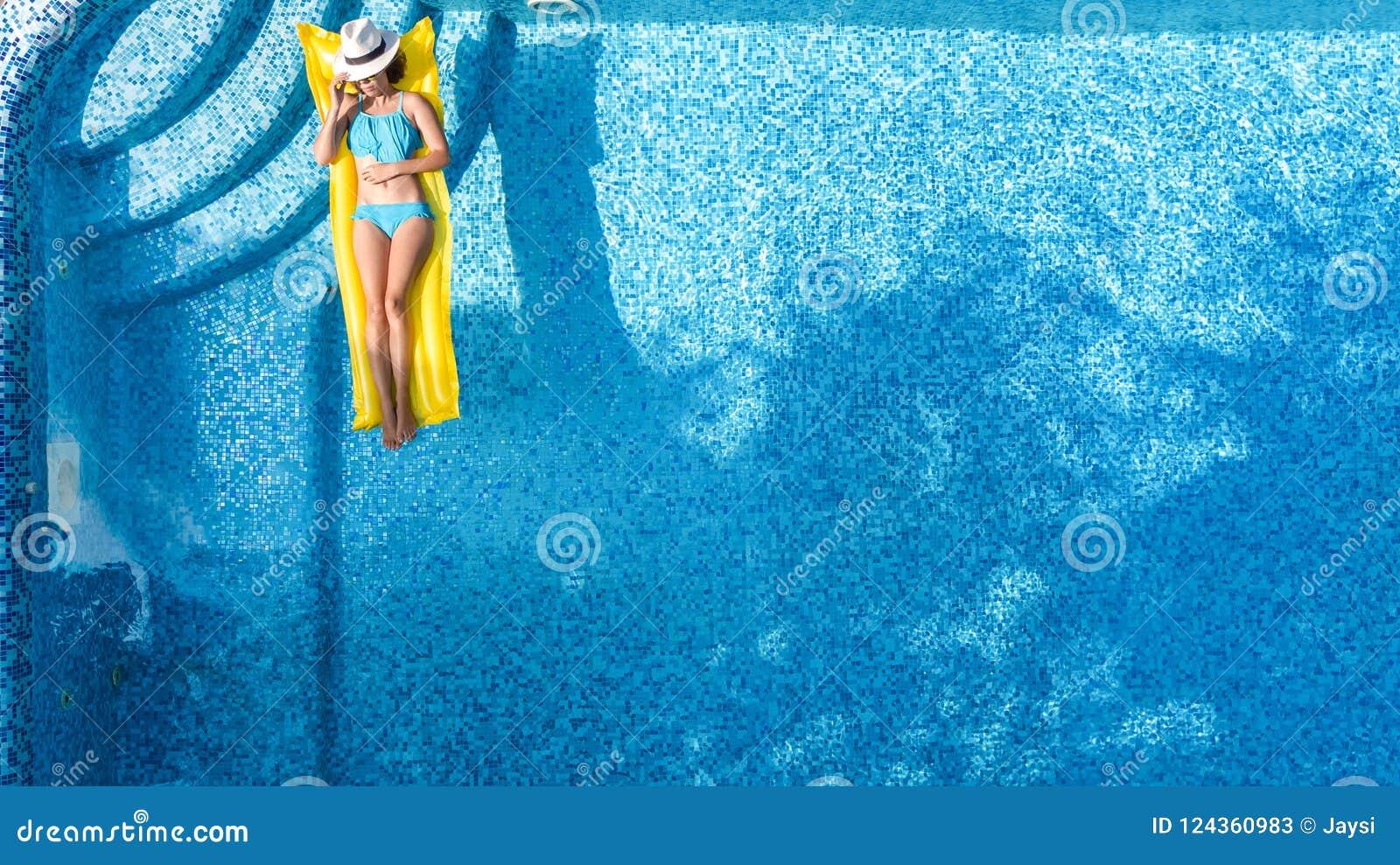 Красивая маленькая девочка ослабляя в бассейне, заплывах на раздувном тюфяке и имеет потеху в воде на семейном отдыхе, виде с воз