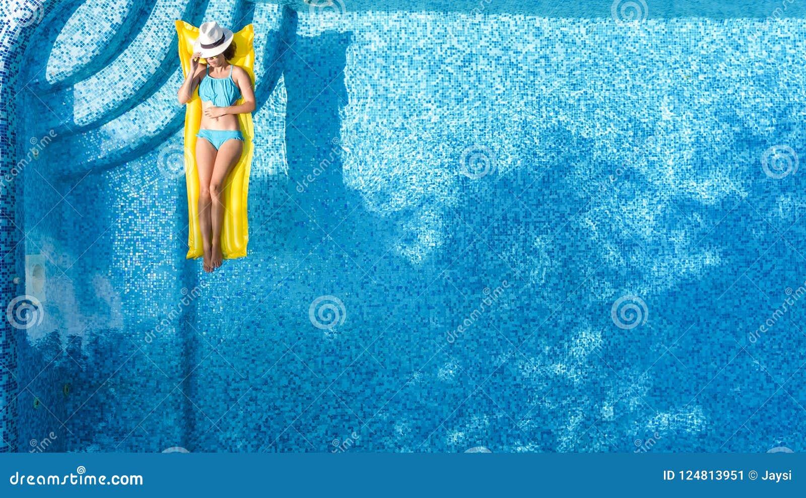 Красивая маленькая девочка ослабляя в бассейне, заплывах на раздувном тюфяке и имеет потеху в воде на семейном отдыхе