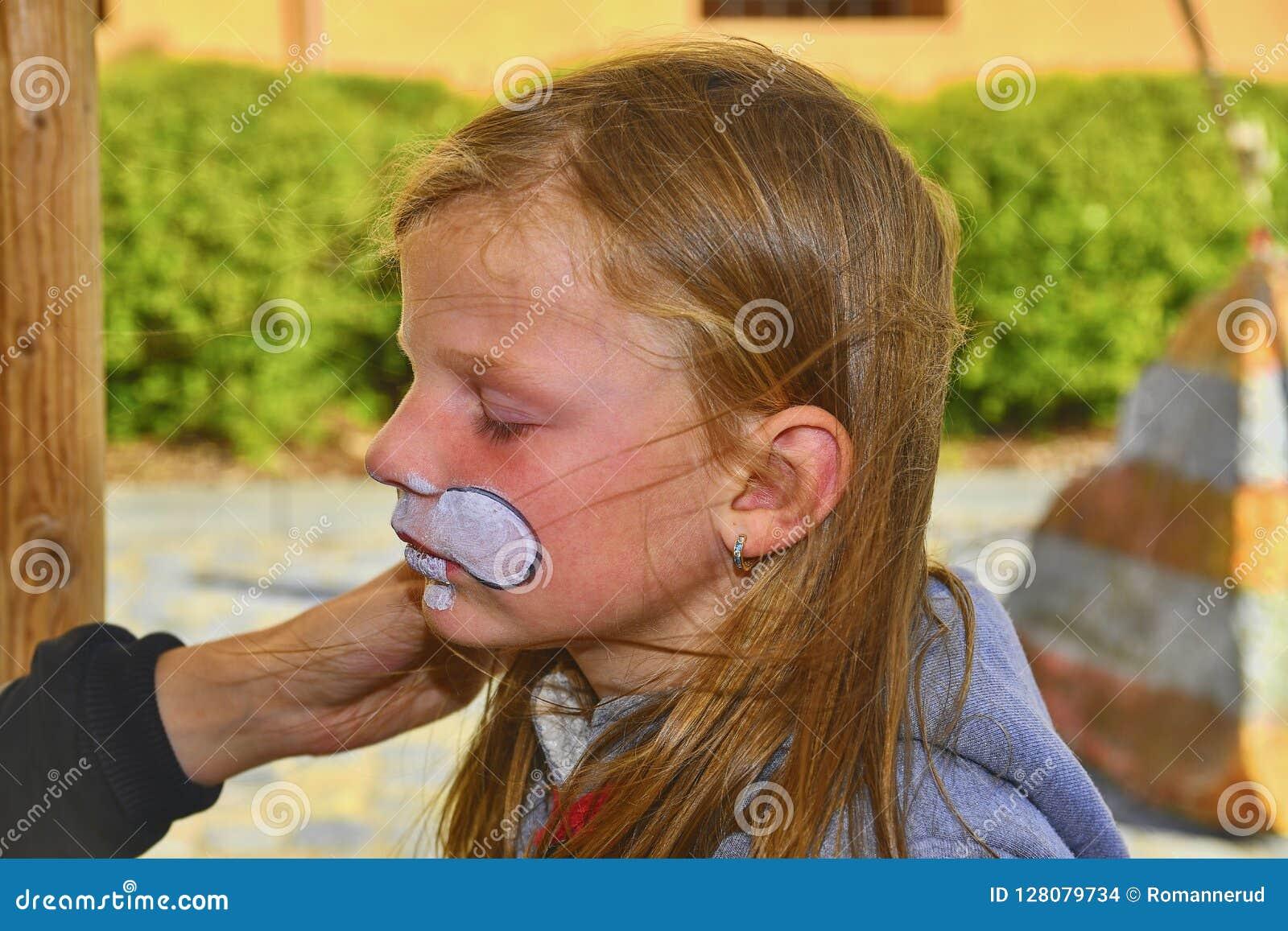 Красивая маленькая девочка при сторона покрашенная как кролик Картина стороны на стороне ребенка