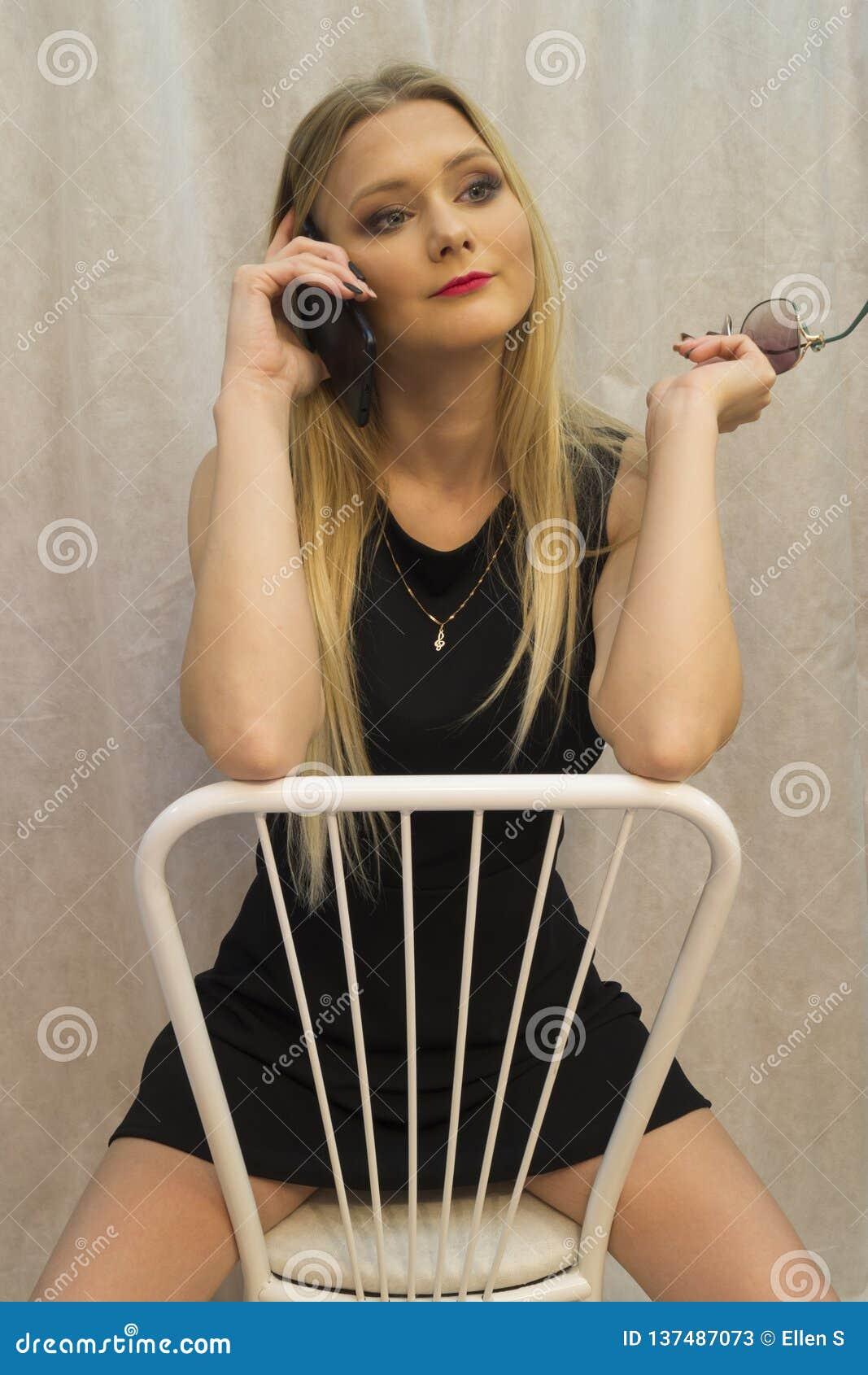 Красивая маленькая девочка сидя на белом стуле и говоря на сотовом телефоне