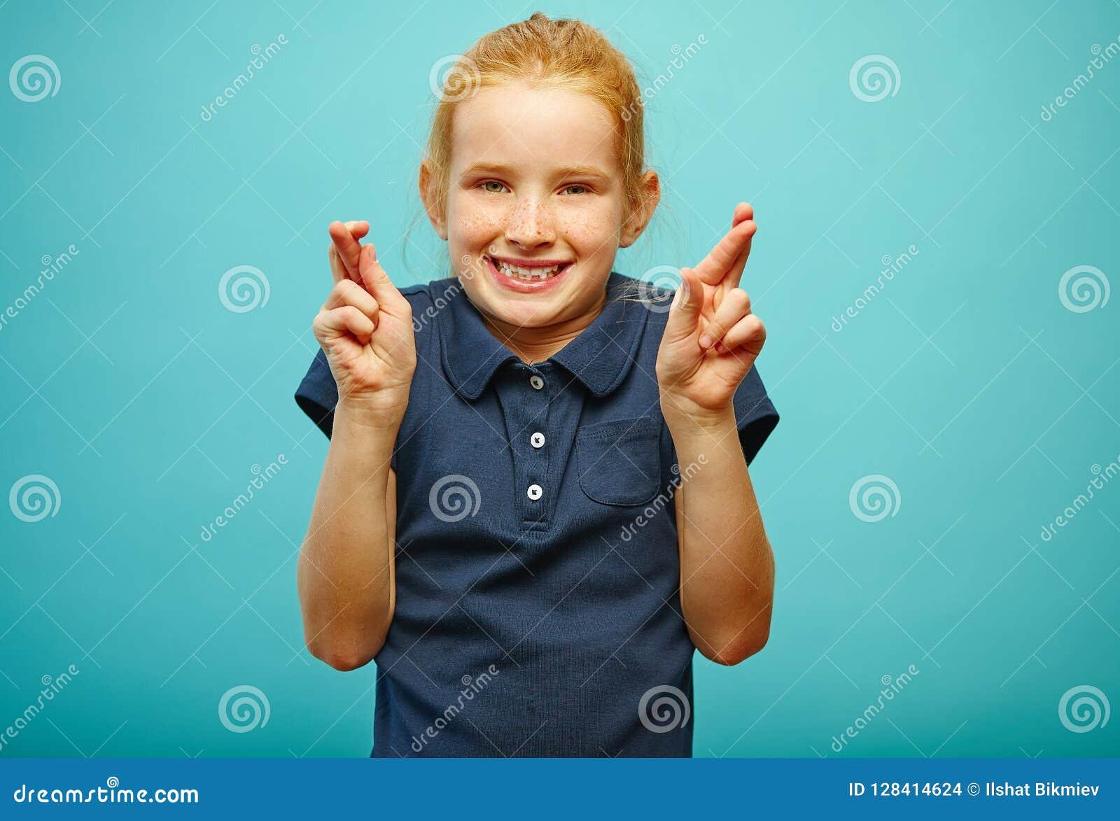 Красивая маленькая девочка с красными волосами и веснушками делает желание, пересеченные пальцы, верит в выполнении мечт, имеет a