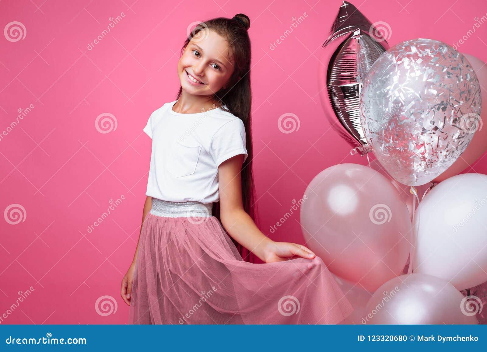 Красивая маленькая девочка, с шариками на розовой предпосылке, празднует день рождения