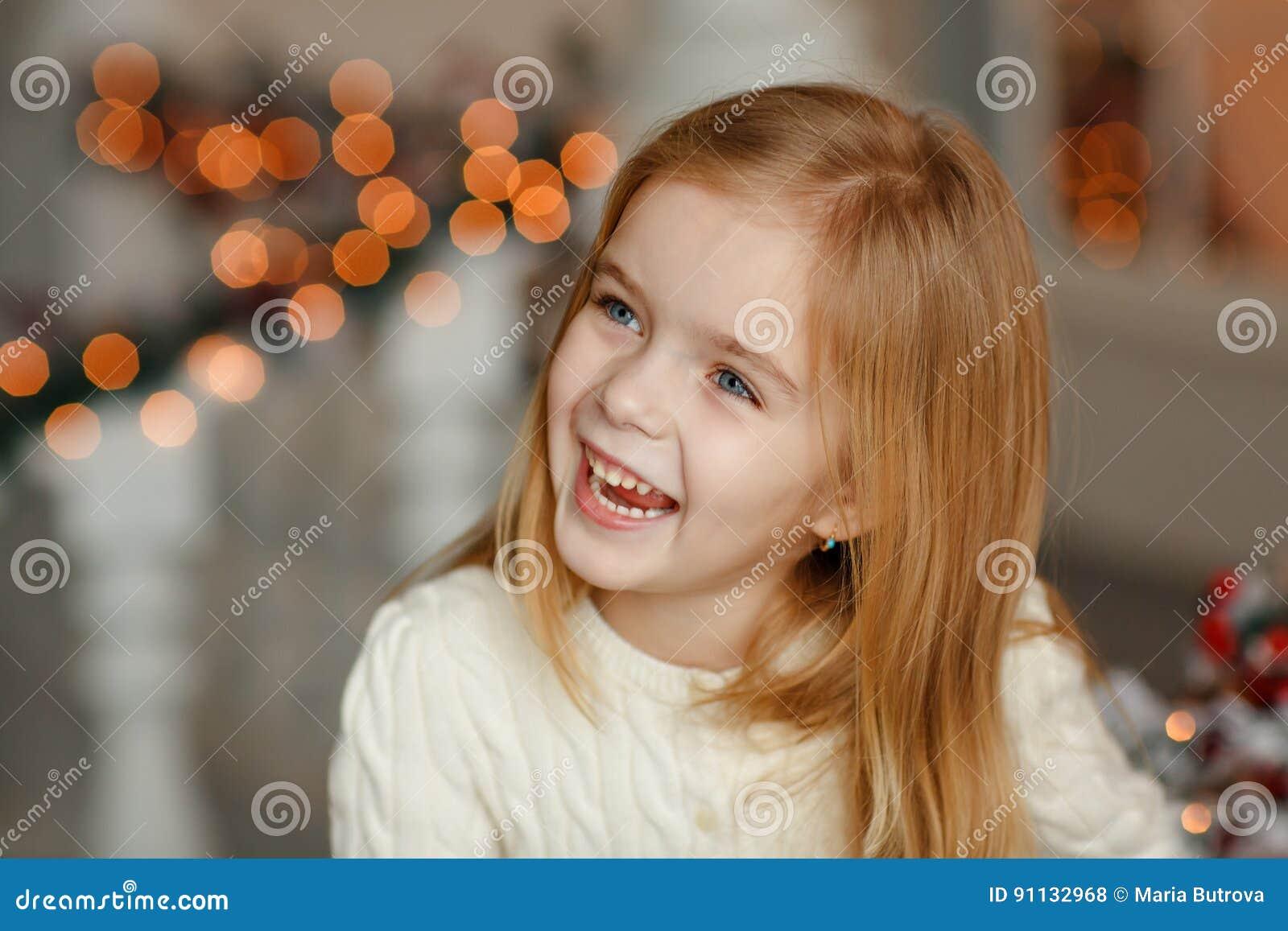 Красивая маленькая белокурая девушка с голубыми глазами усмехаясь на новом Ye