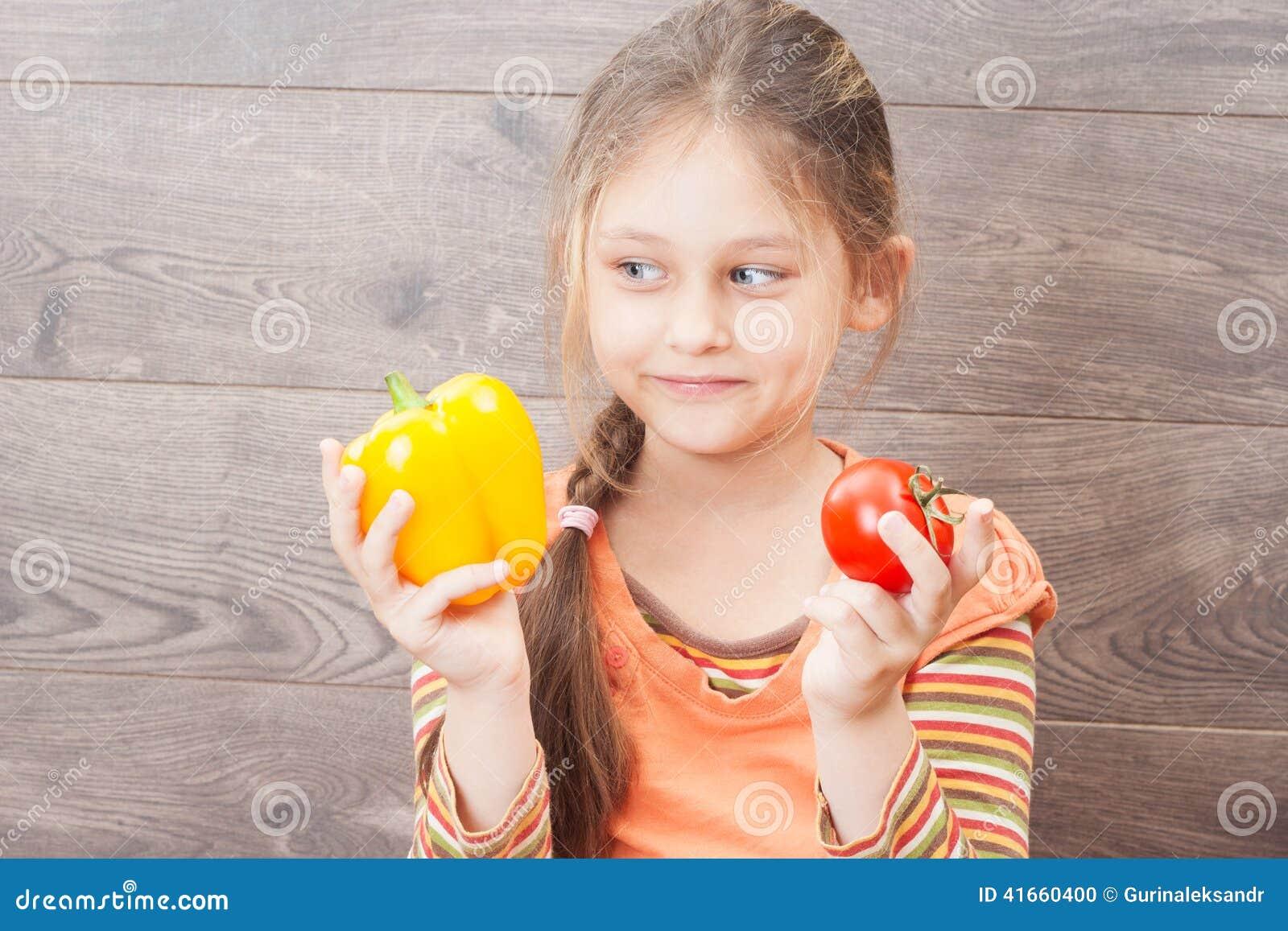 Красивая маленькая девочка держит свежие овощи