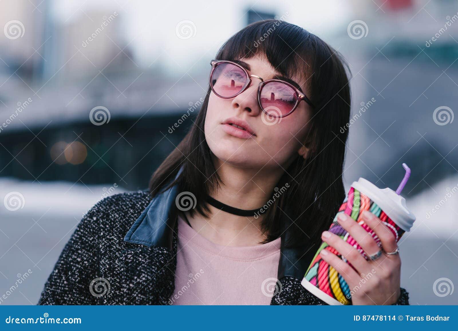 Красивая маленькая девочка одела весной стекла битника розовые держа красочную чашку горячего питья