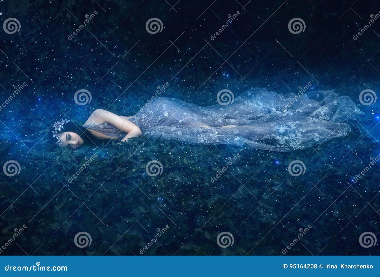 Красивая маленькая девочка спит в оружиях космоса