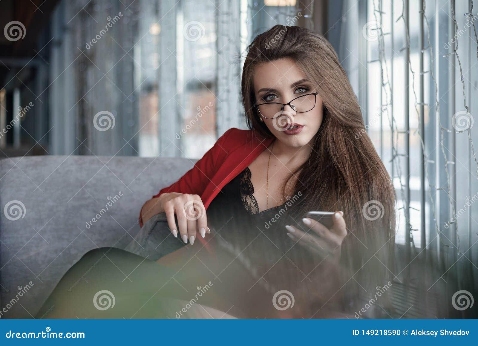 Красивая милая молодая коммерсантка в кафе, используя мобильный телефон и выпивая усмехаться кофе