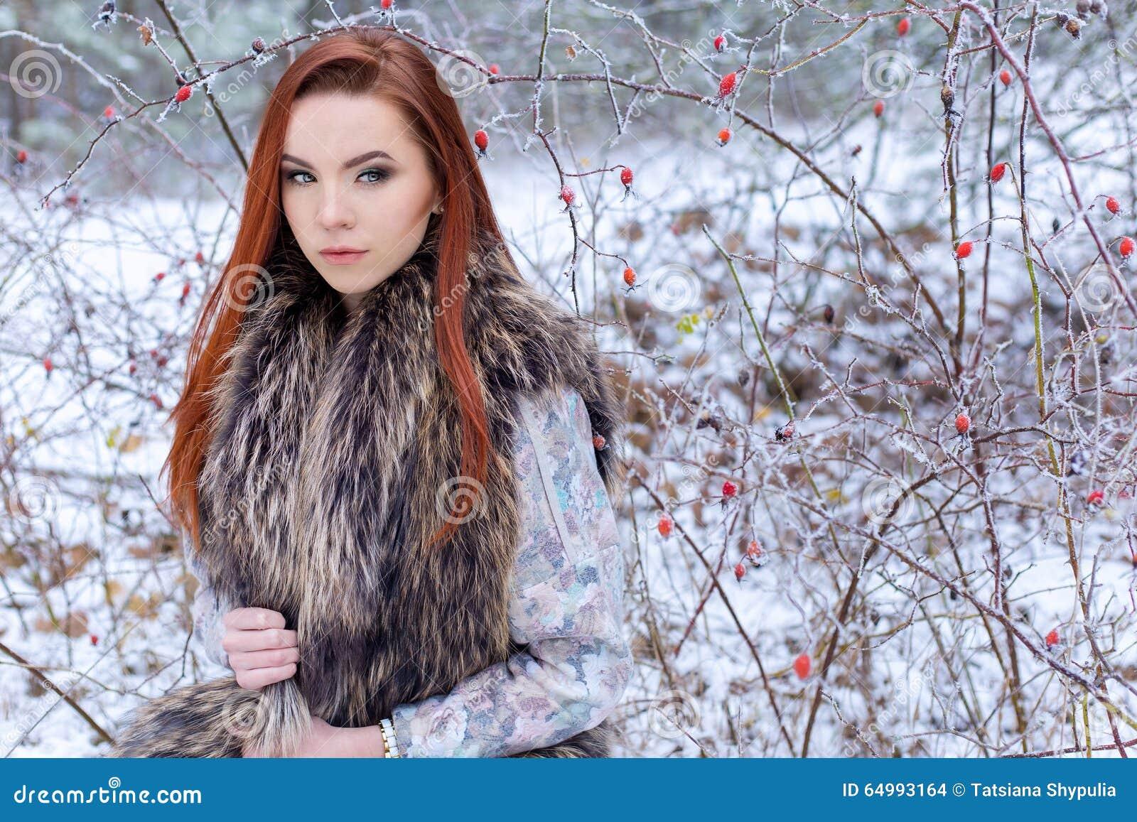 Красивая милая сексуальная маленькая девочка с красными волосами идя в снежный лес среди деревьев пропустила первые кусты trimest