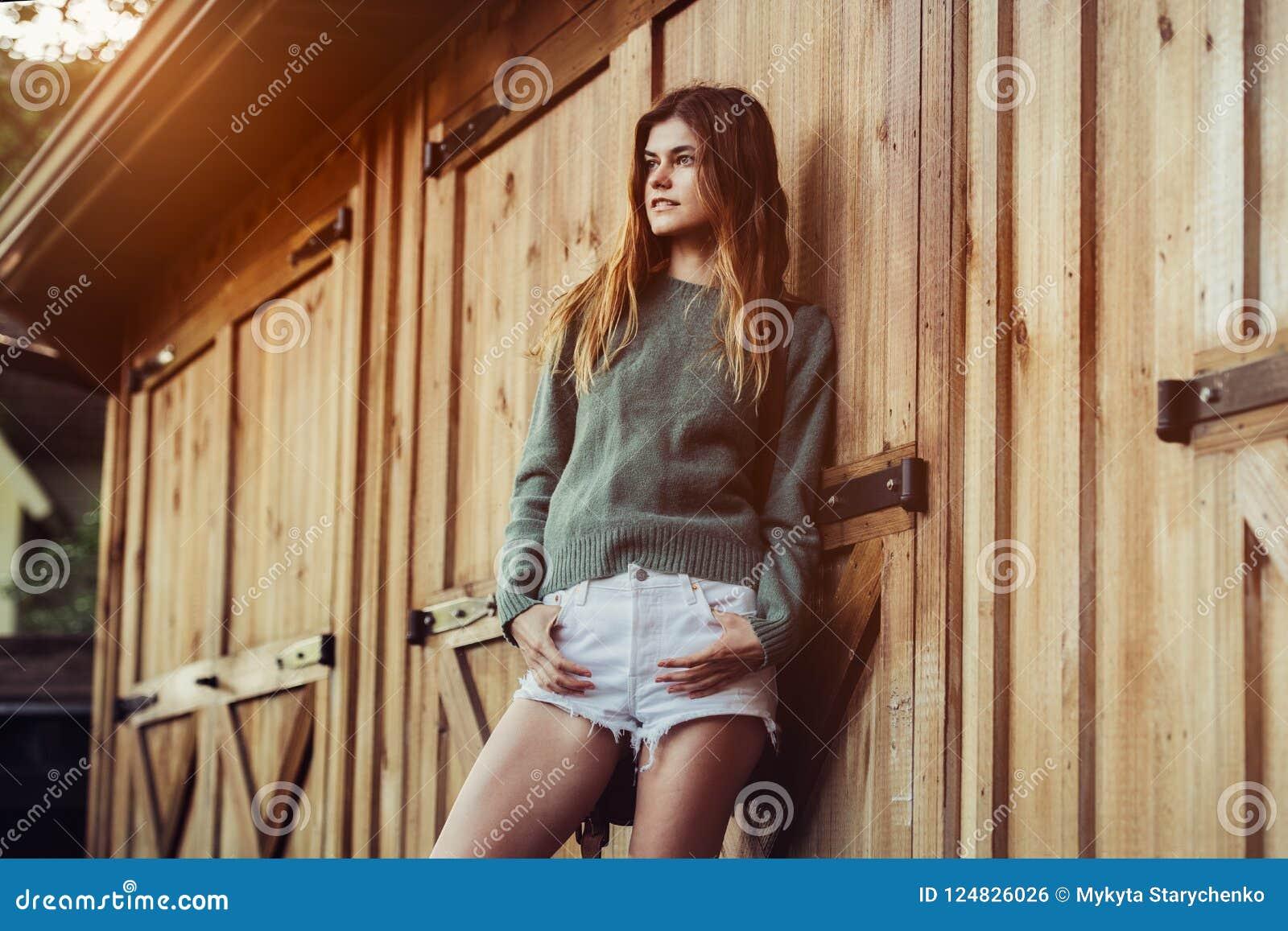Красивая молодая взрослая женщина страны представляя около дверей фермы амбара деревянных на шортах времени захода солнца нося бе