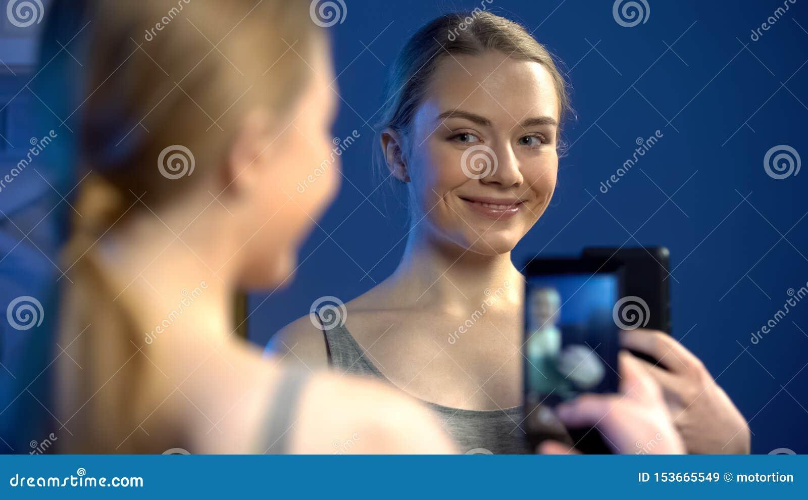 Красивая молодая дама делая selfie в отражении зеркала для социальных сетей, потехе