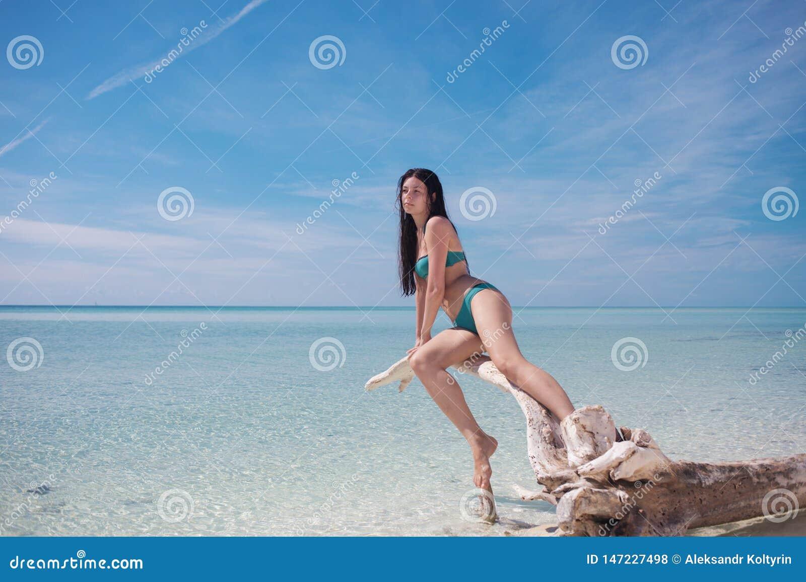 Красивая молодая женщина в бикини в океане Молодой привлекательный брюнет в голубом купальнике в открытом море
