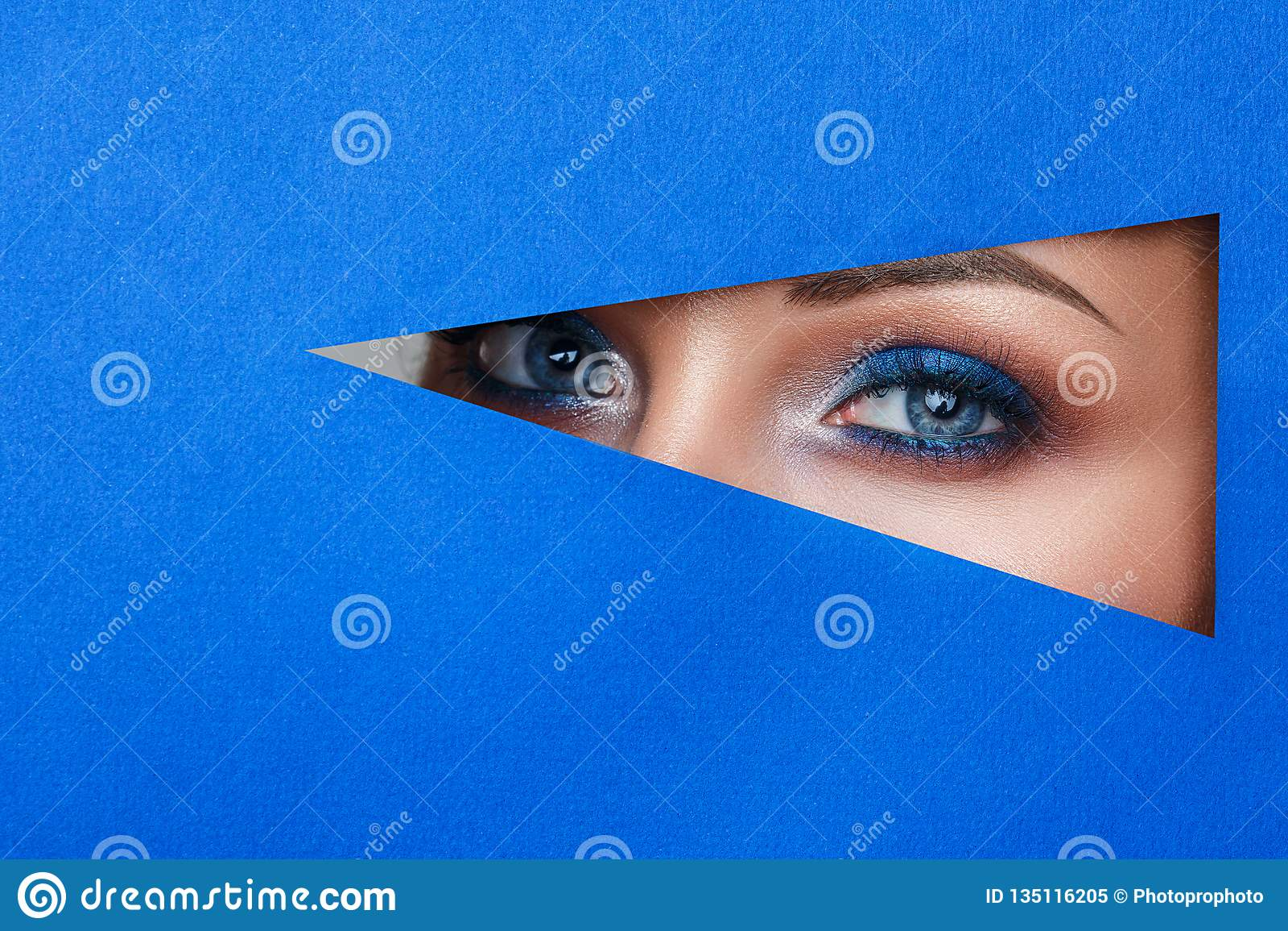 Красивая молодая женщина в отверстии в голубой бумаге, красивом ярком макияже