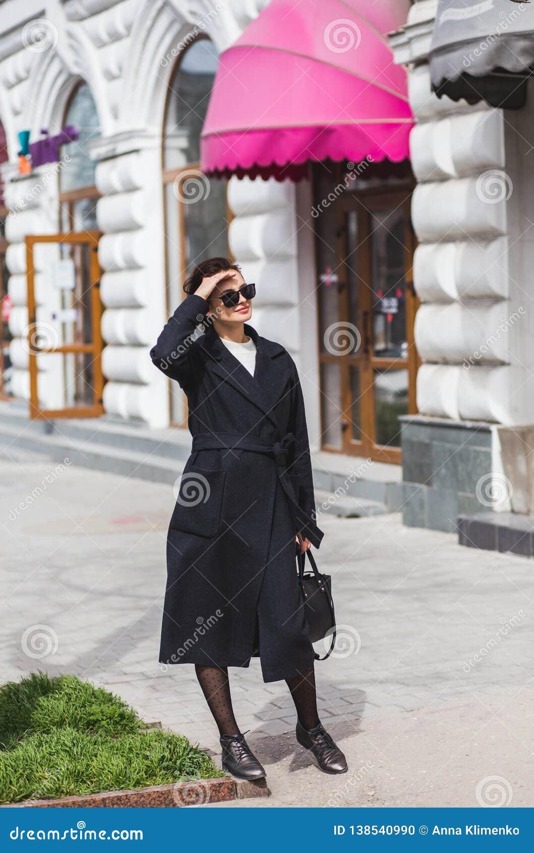 Красивая молодая женщина идя на улицу делая покупки