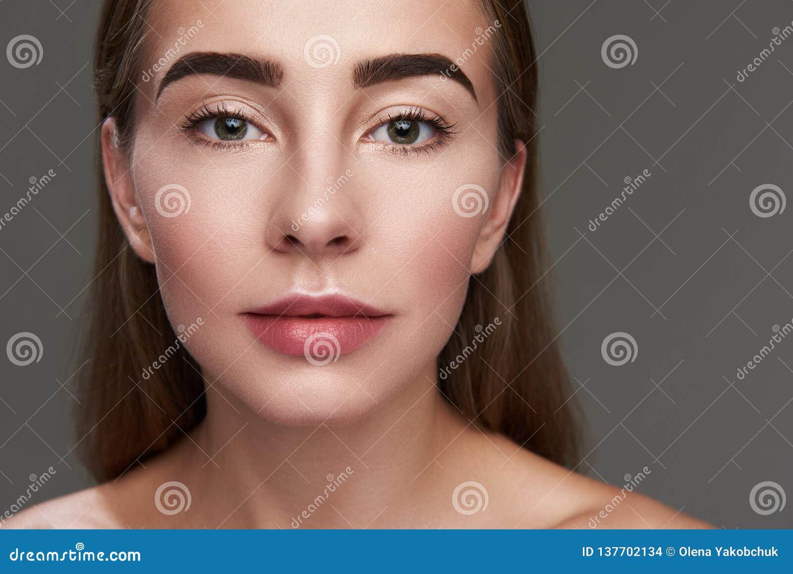 Красивая молодая женщина представляя на серой предпосылке