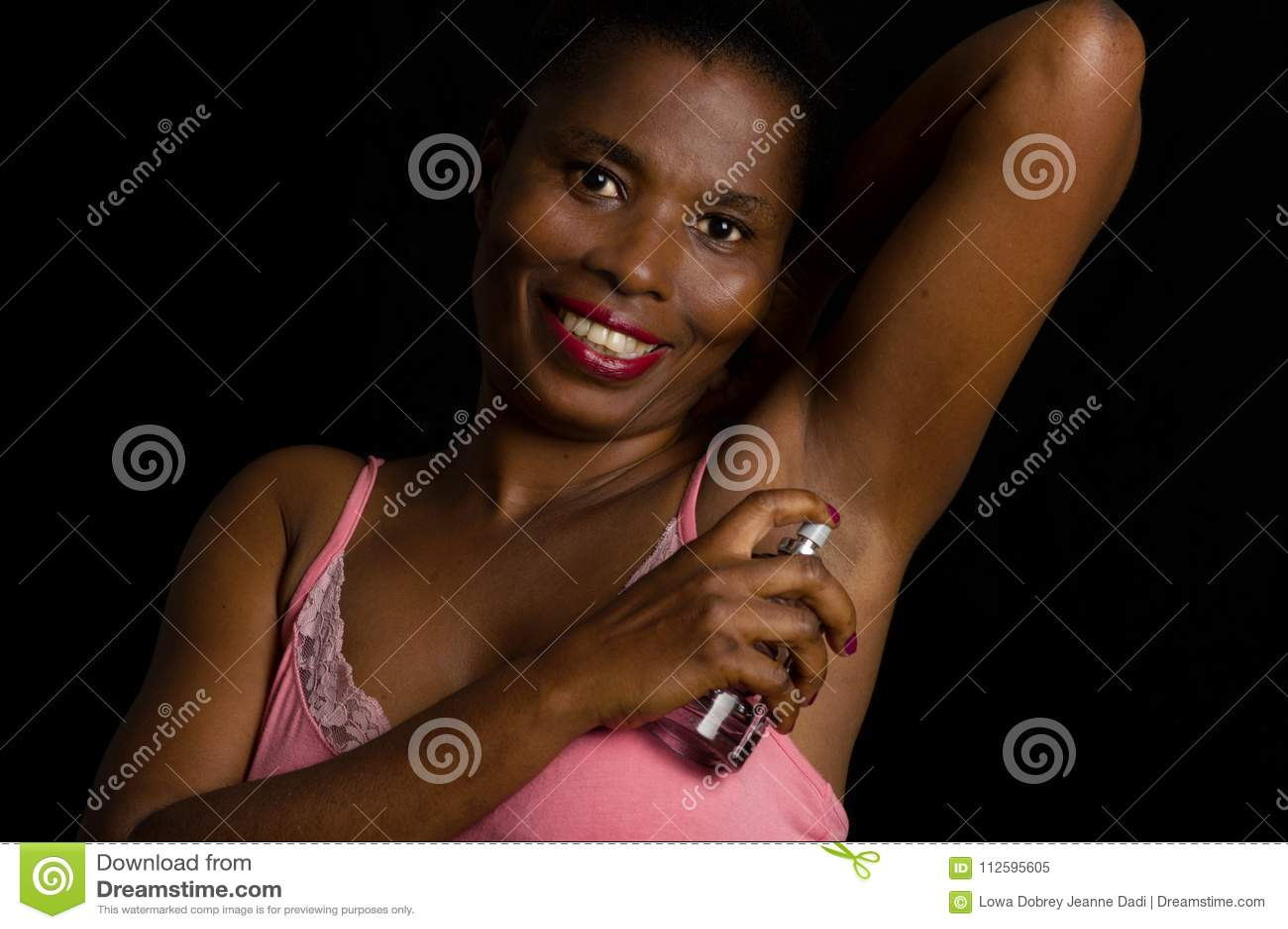 Красивая молодая женщина прикладывая дух подмышки на темной предпосылке