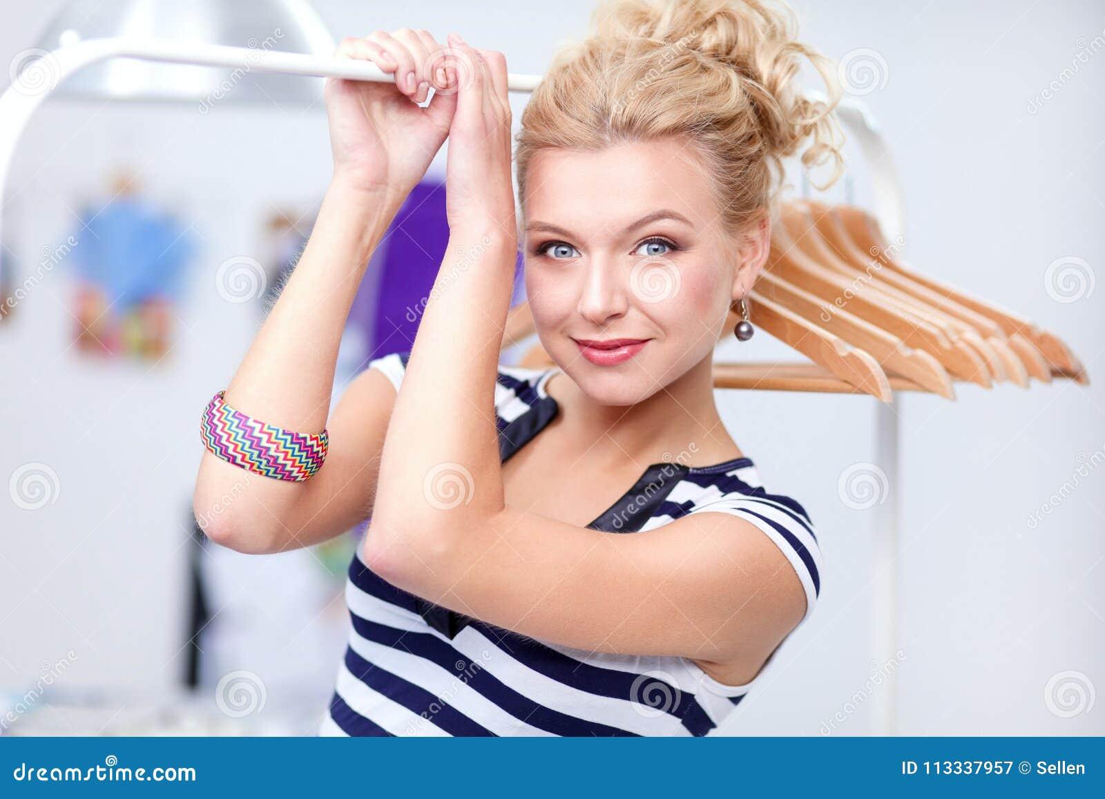 Красивая молодая женщина стилизатора около шкафа с вешалками