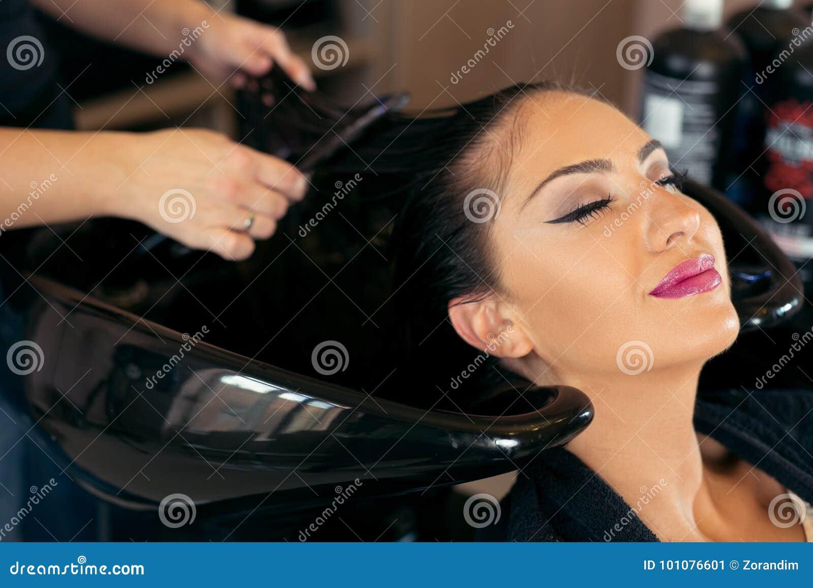 Красивая молодая женщина с головой парикмахера моя на парикмахерской