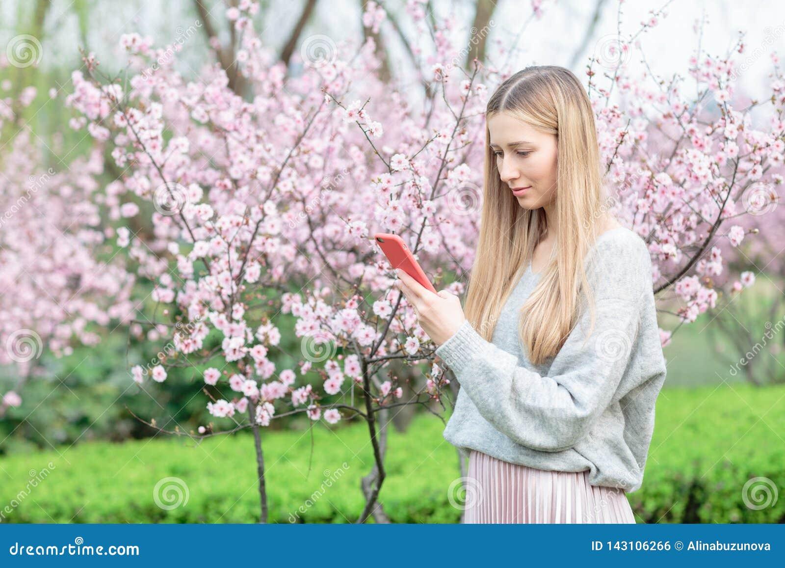 Красивая молодая женщина с длинными светлыми волосами используя мобильный телефон в парке с зацветая деревом