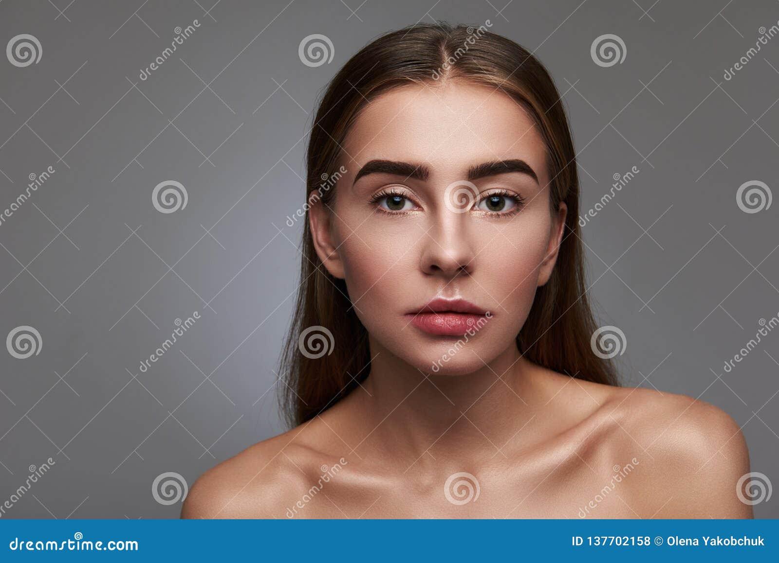 Красивая молодая женщина с естественным макияжем представляя против серой предпосылки