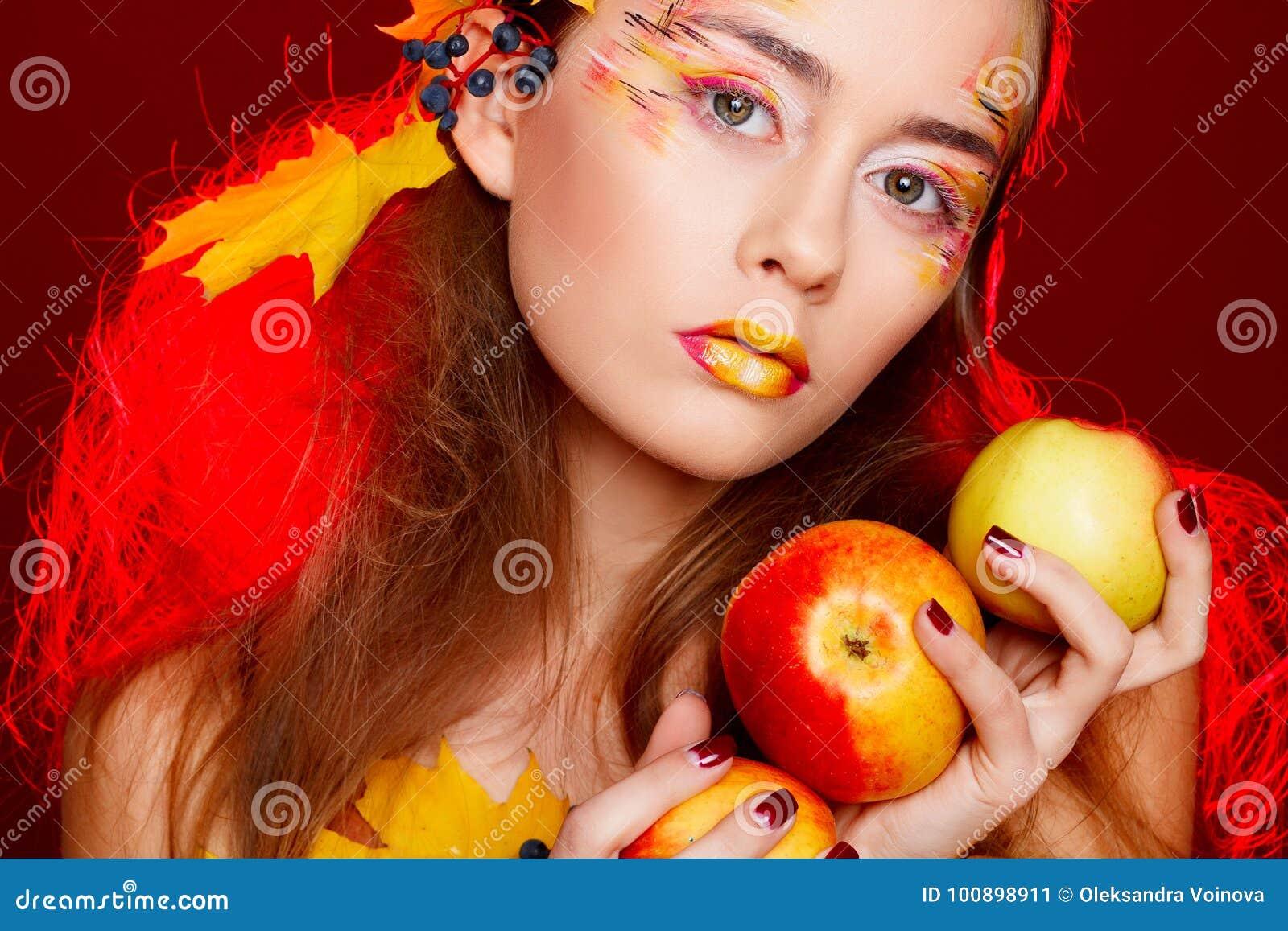 Красивая молодая женщина с осенью составляет представлять в студии сверх