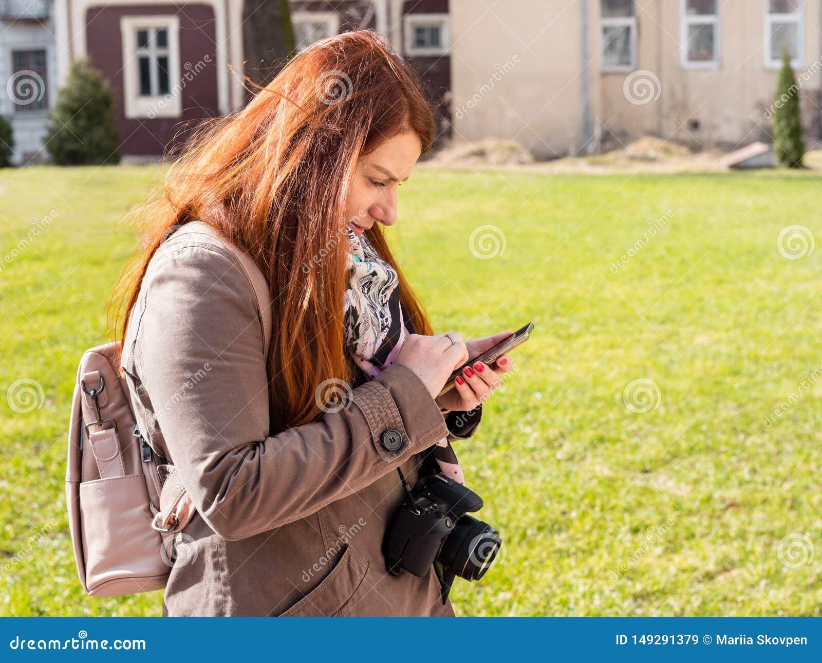 Красивая молодая женщина redhead видит умный телефон в парке