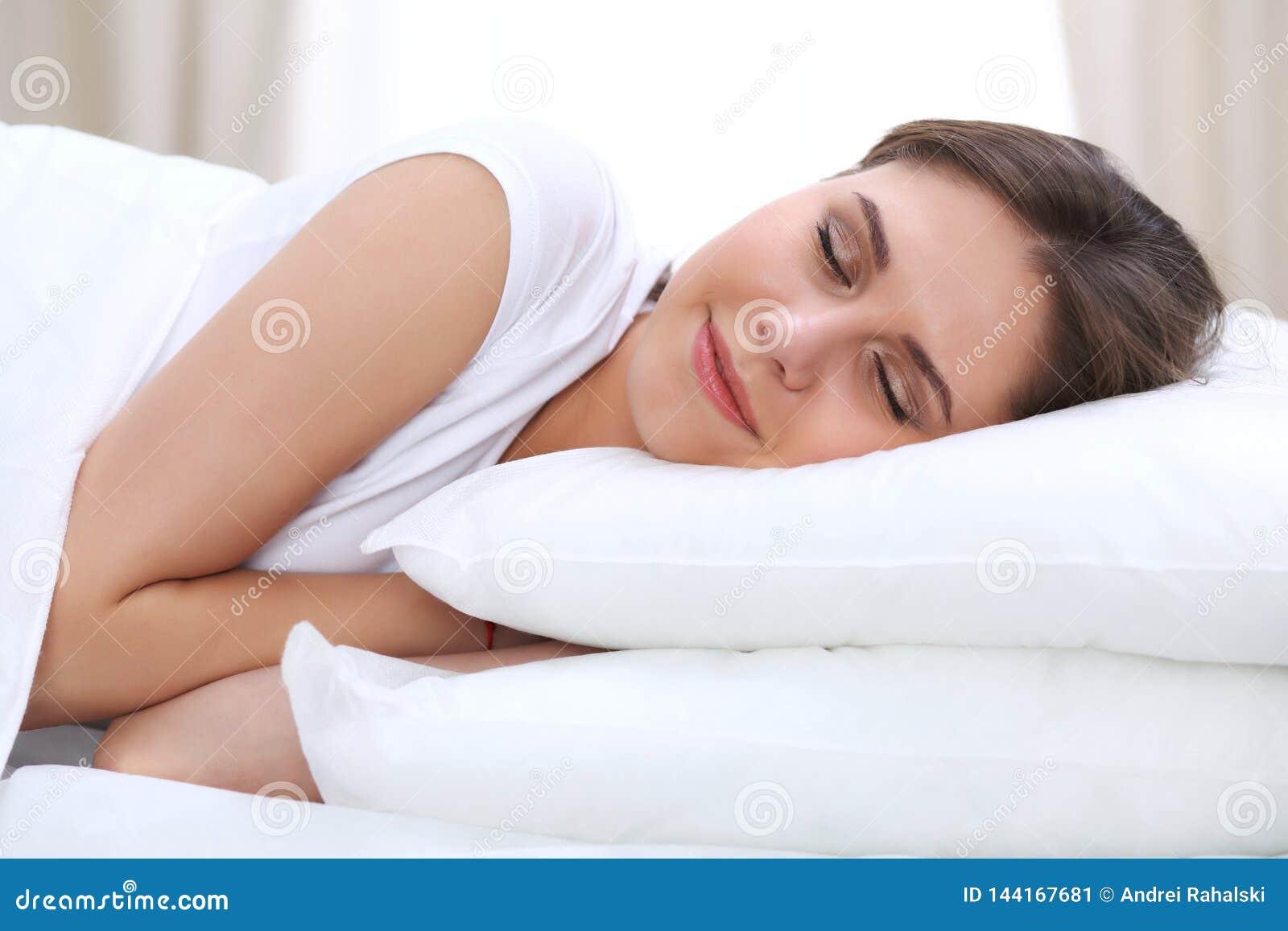 Красивая молодая и счастливая женщина спать пока лежащ в кровати удобно и блаженно усмехающся