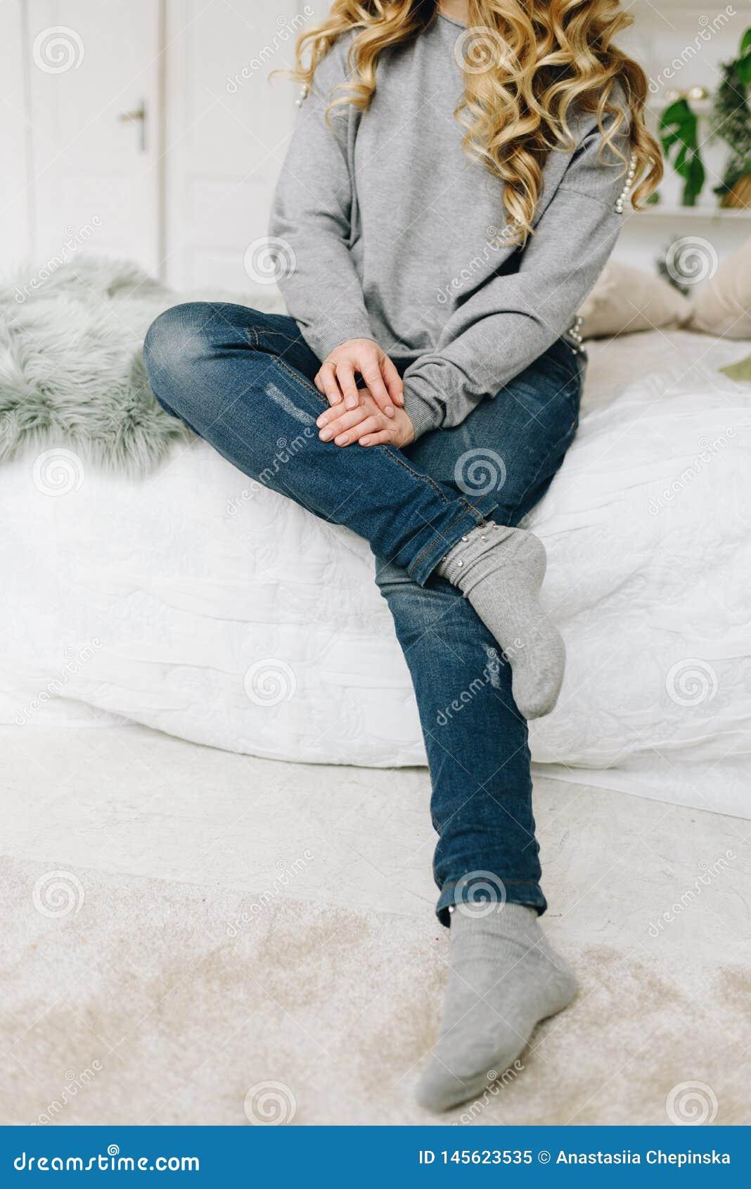 Красивая молодая кавказская европейская женщина случайно сидя на кровати