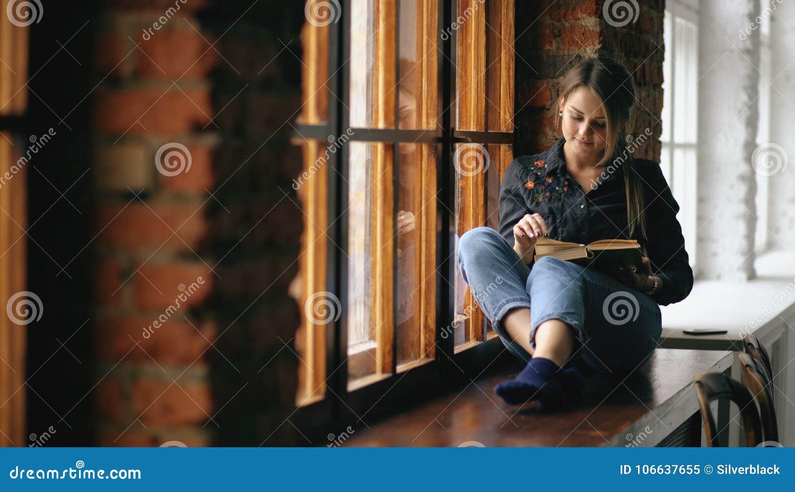 Красивая молодая книга чтения девушки студента сидит на windowsill в классе университета внутри помещения