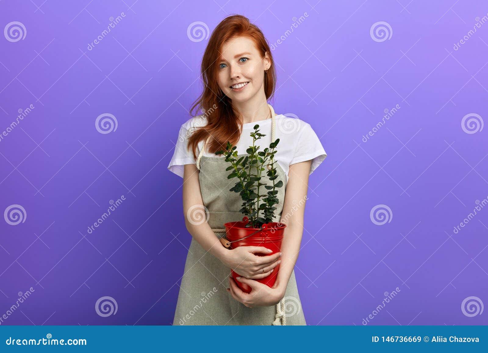Красивая молодая усмехаясь рыжеволосая женщина держа бак цветка