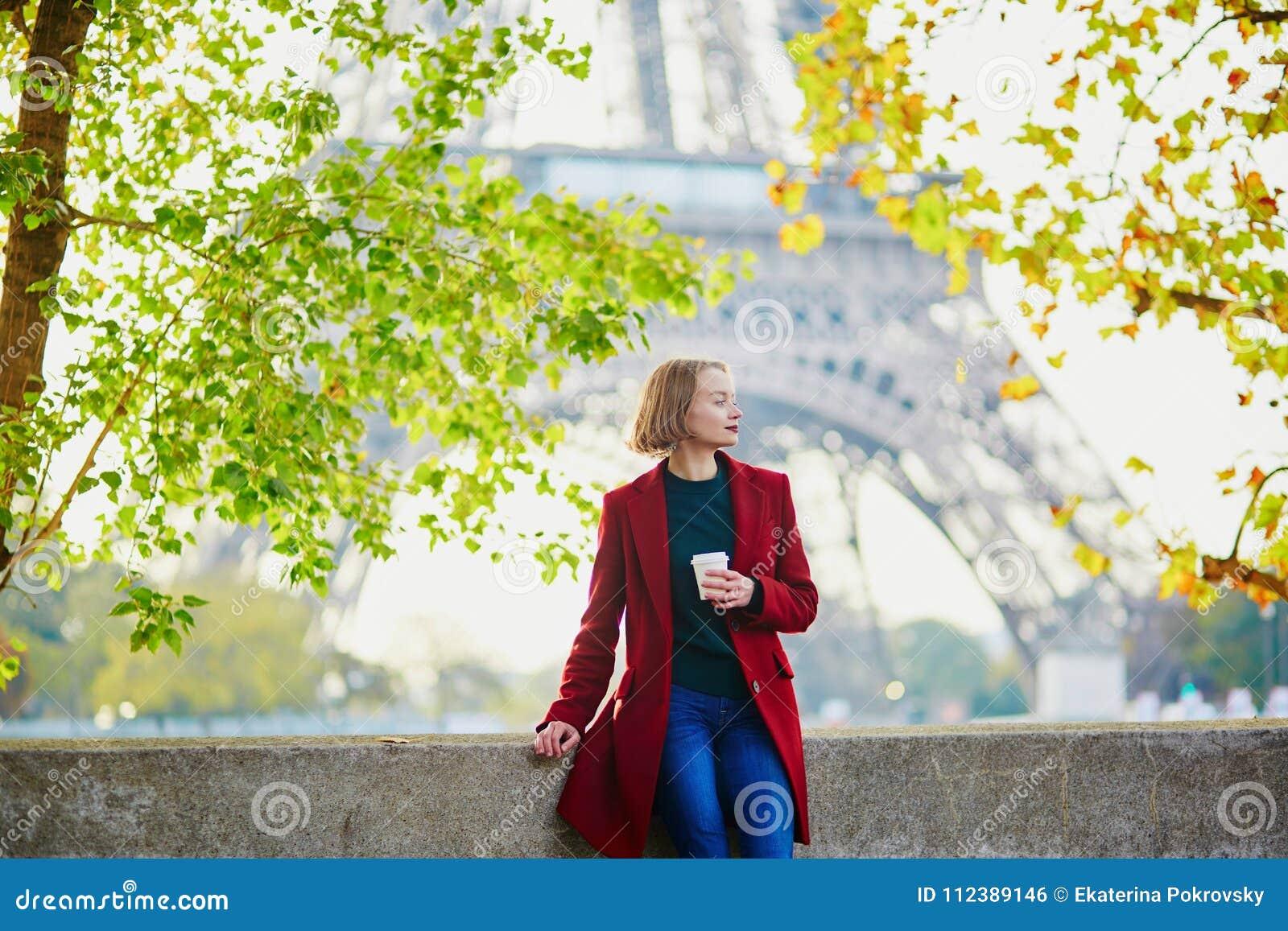 Красивая молодая французская женщина около Эйфелевой башни в Париже