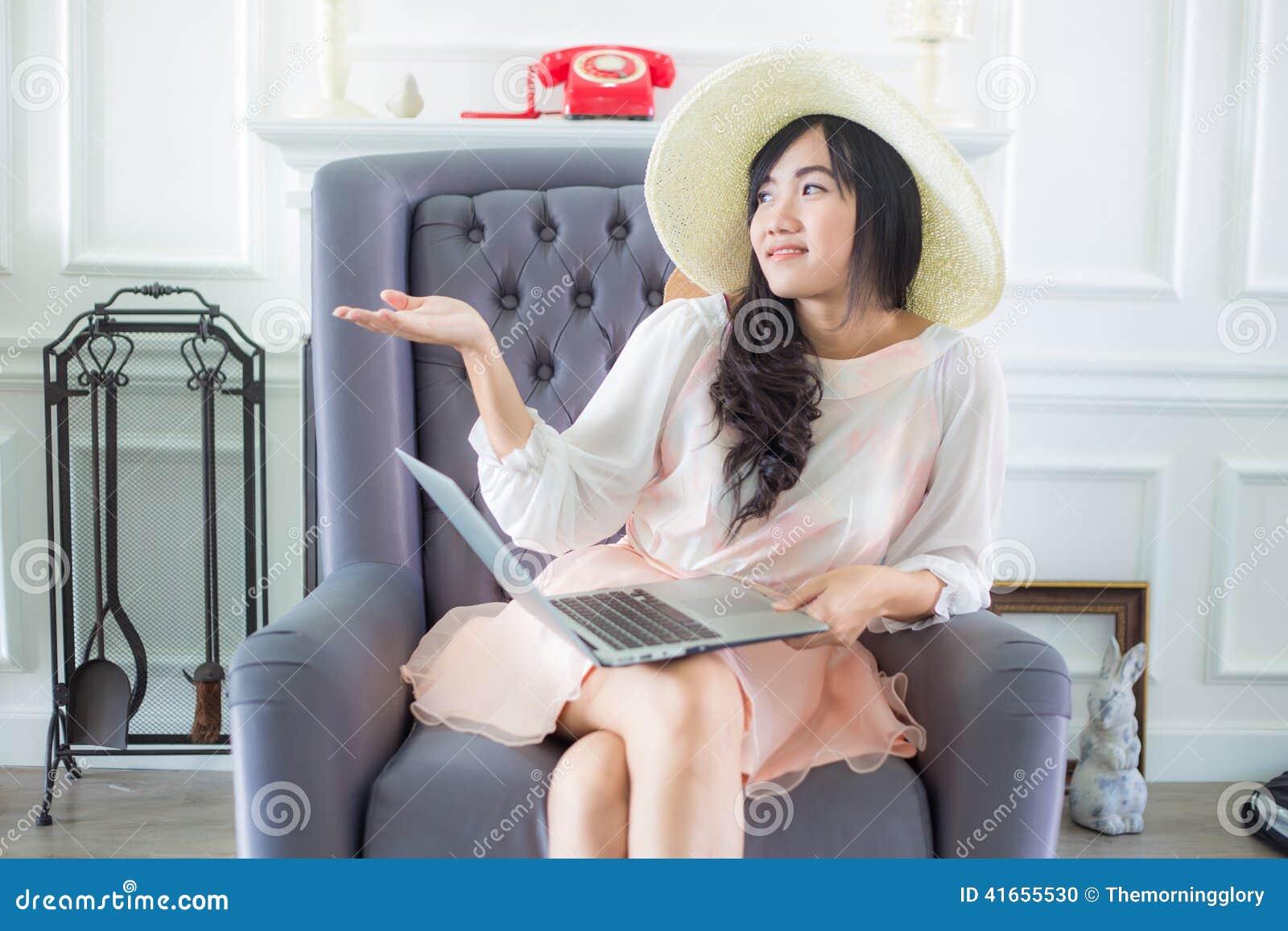 Красивая молодая азиатская женщина дома сидя на роскошном usi софы