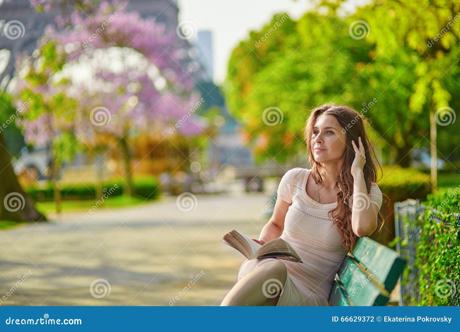 Красивая молодая женщина в чтении Парижа на стенде outdoors