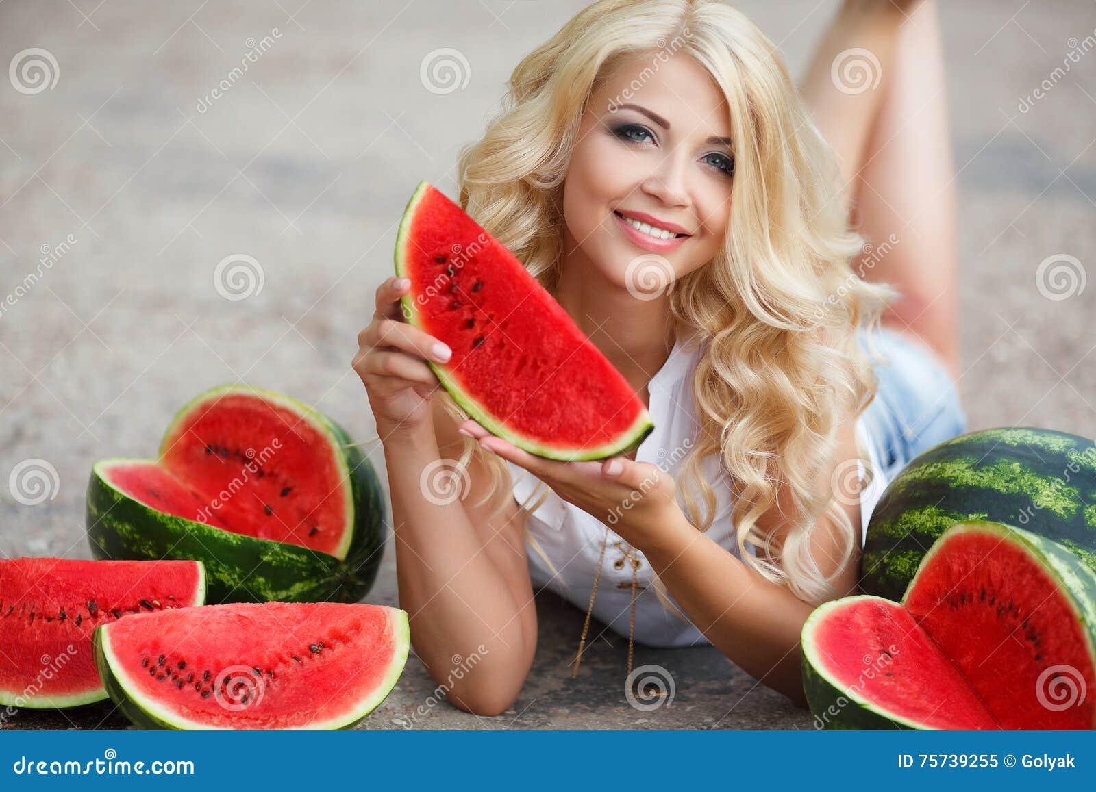 Красивая молодая женщина держа кусок зрелого арбуза