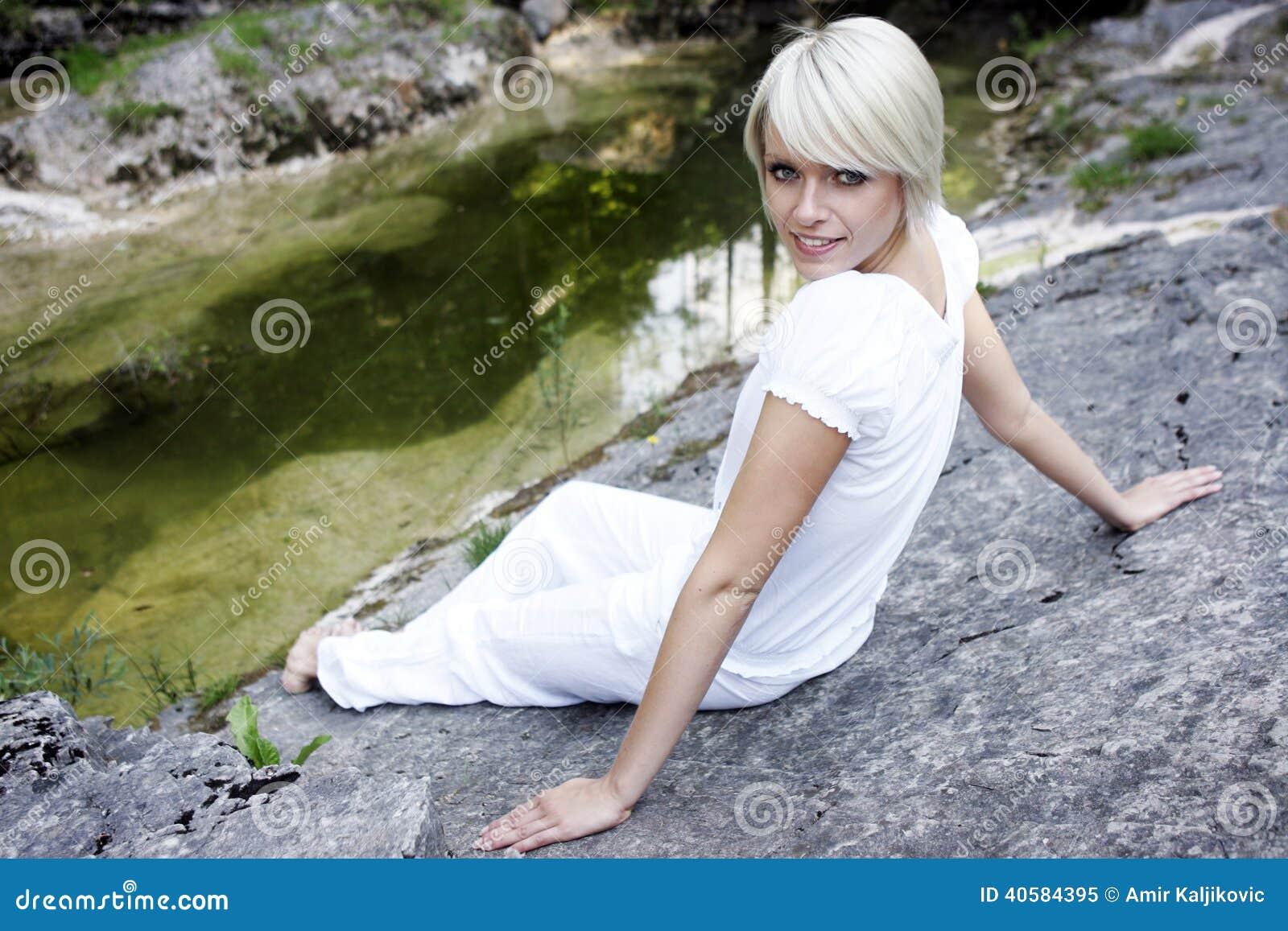 Красивая молодая женщина ослабляя на утесе