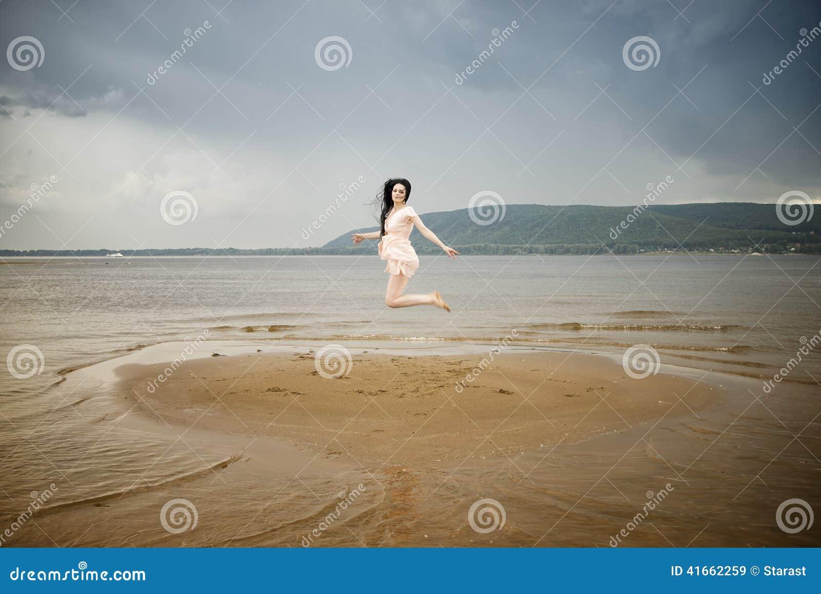 Красивая молодая женщина скача на песчаный пляж