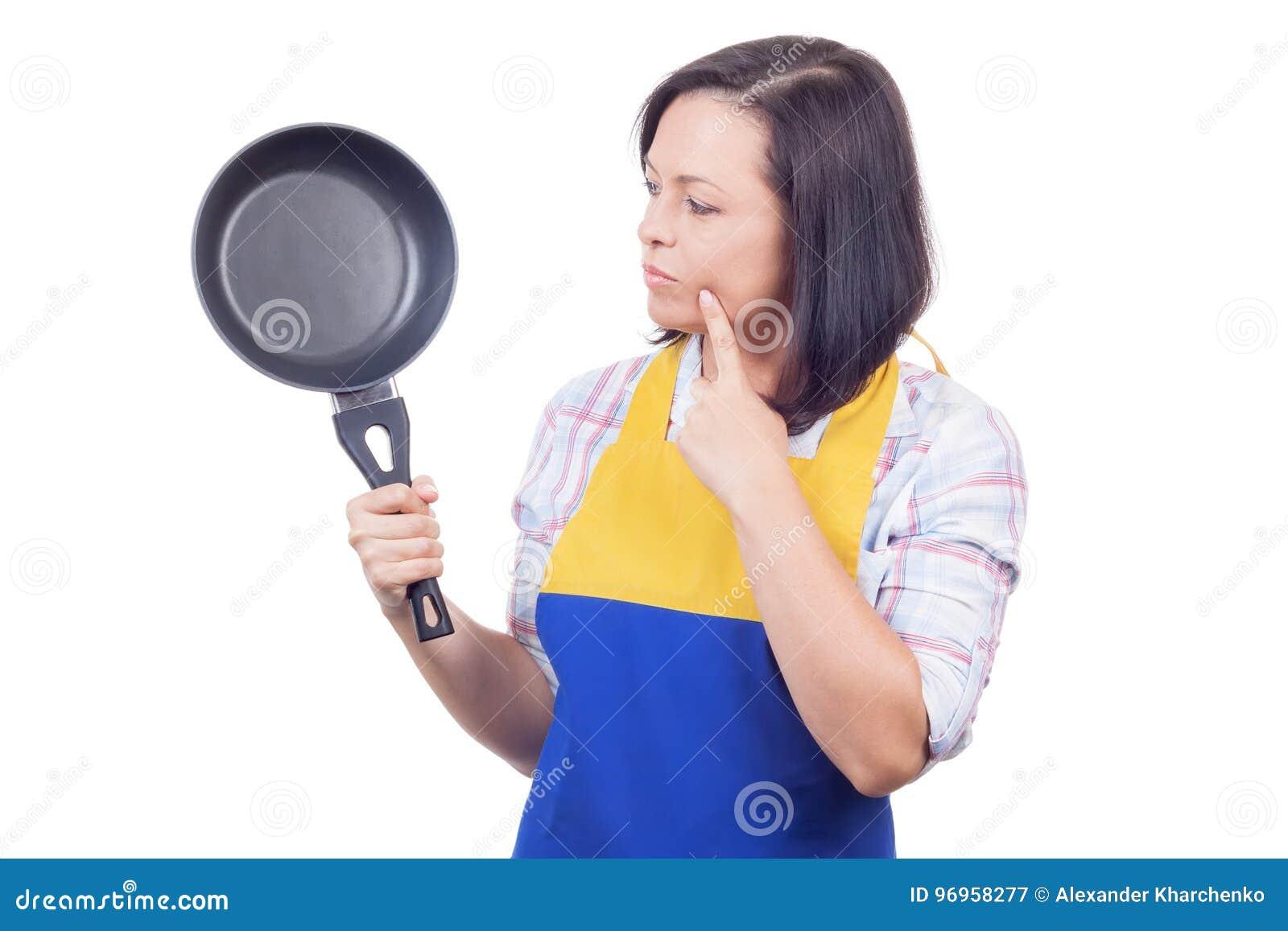 Красивая молодая женщина с сковородой думая что подготовить f