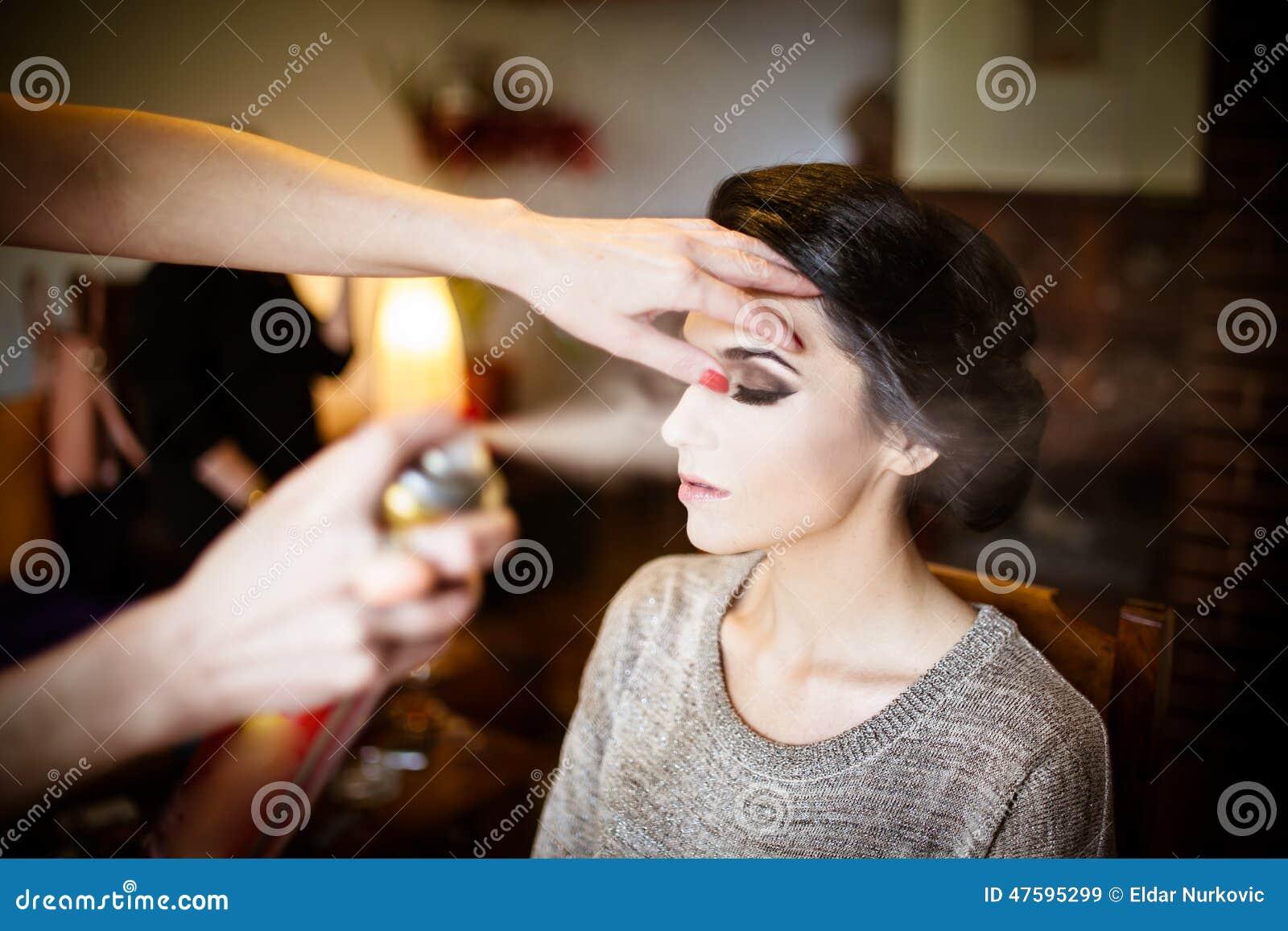 Красивая невеста делая ее волосы и состав Спрей для волос парикмахера распыляя на ее updo