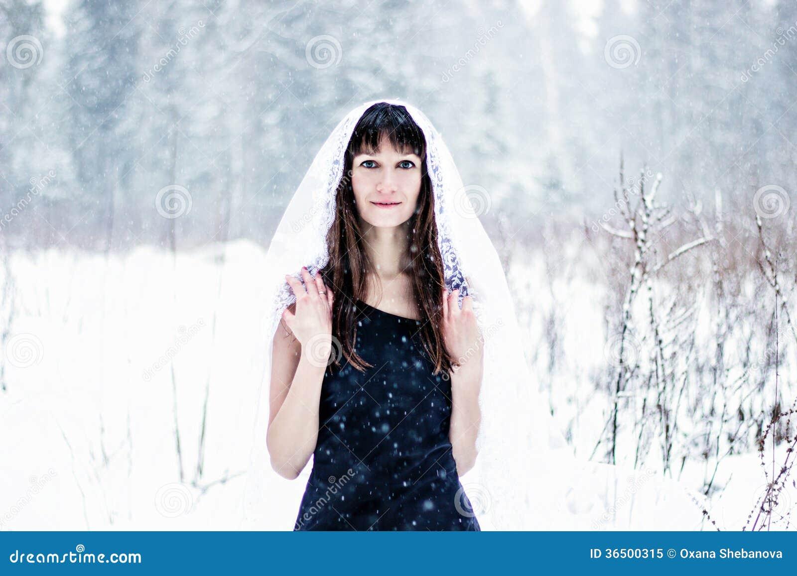 Красивая невеста под вуалью на белой предпосылке снега