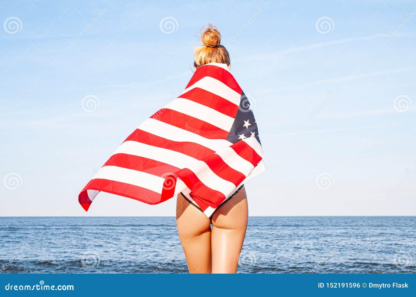 Красивая патриотическая женщина с американским флагом на пляже День независимости США, 4-ое июля :