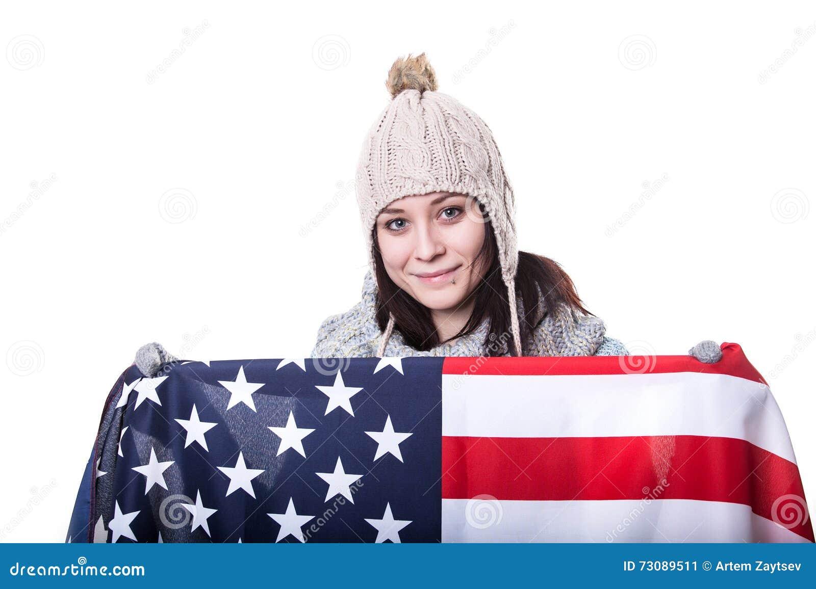 Красивая патриотическая vivacious молодая женщина при американский флаг, который держат в ей протягивала руки стоя перед