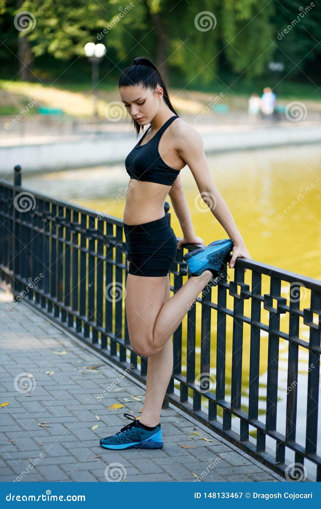 Красивая подходящая женская модель девушки фитнеса делая простирание работая после разминки снаружи озером летом