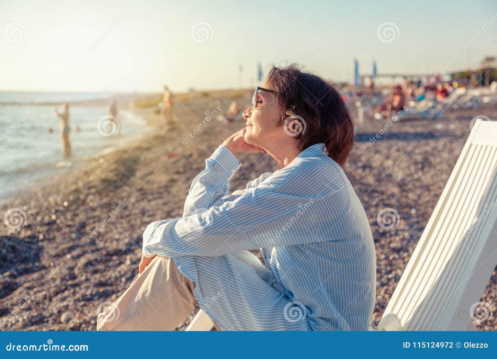 Красивая пожилая женщина сидя в deckchair на пляже и