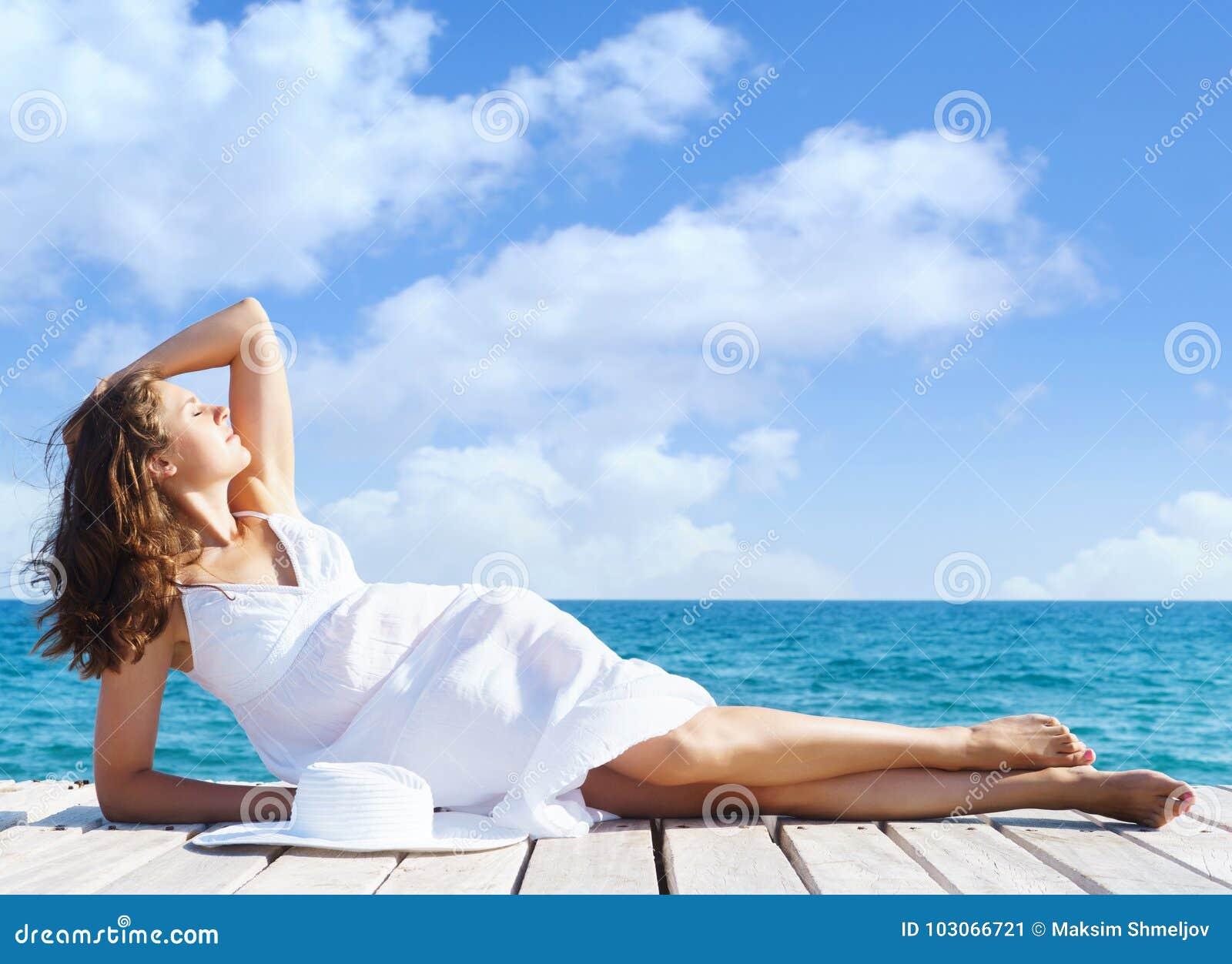 Красивая, привлекательная модель представляя в белом платье на деревянном pi