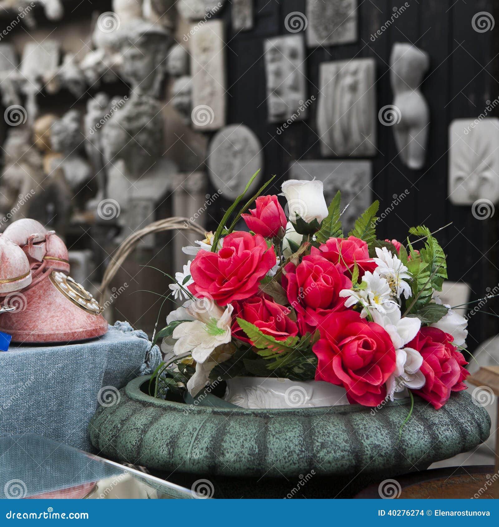 Красивая роза искусственных цветков и старого розового телефона с диском