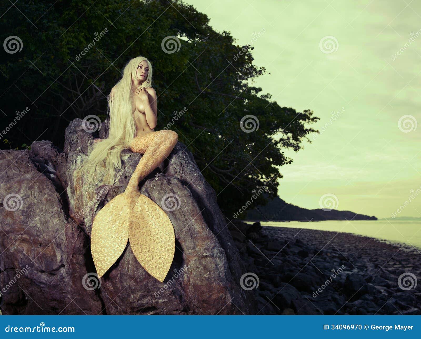 Красивая русалка сидя на утесе